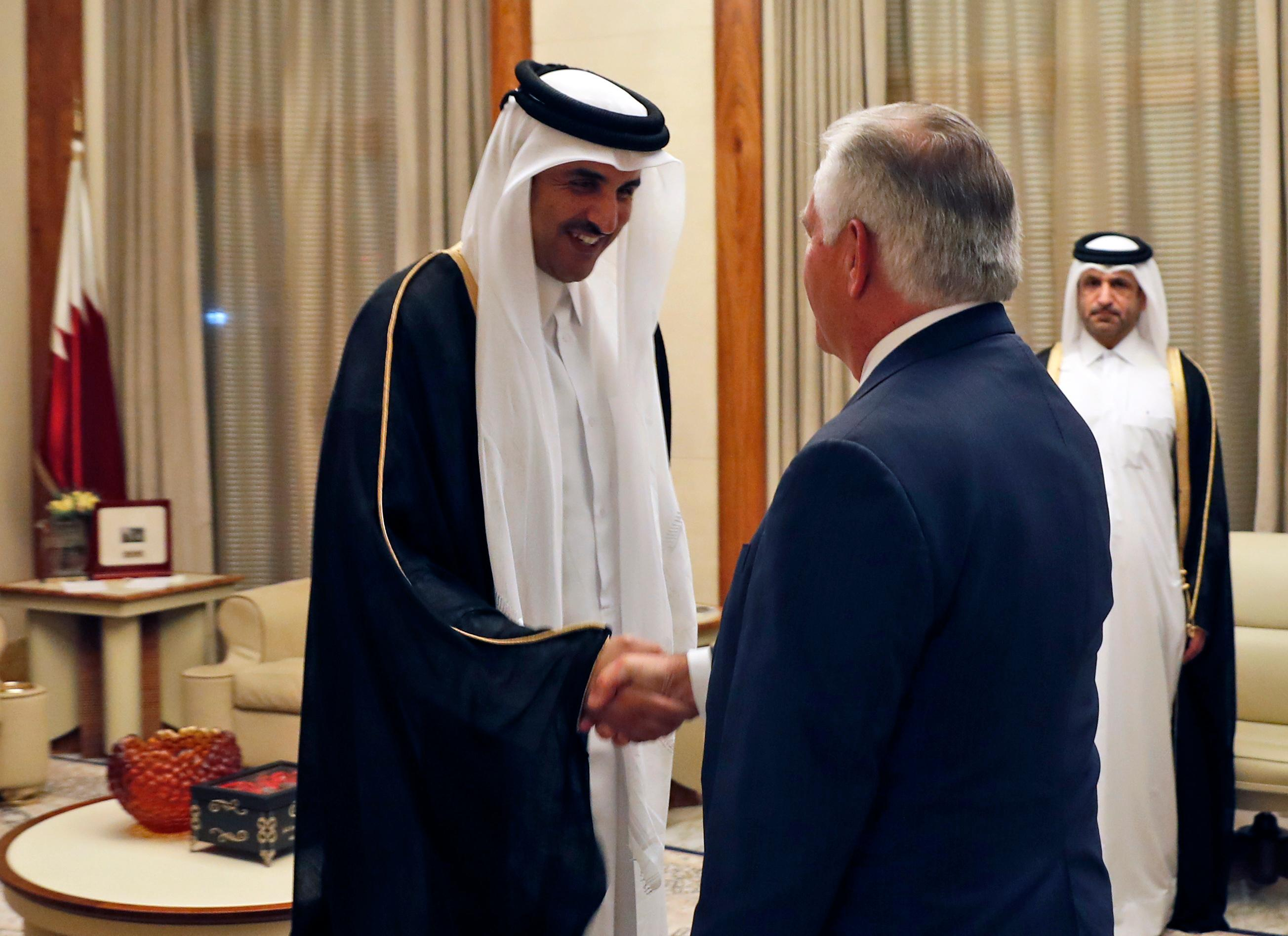 Secretary of State Rex Tillerson, right, shakes hands with Qatar's Emir Sheikh Tamim bin Hamad Al Thani before a meeting, Sunday, Oct. 22, 2017, in Doha, Qatar. (AP Photo/Alex Brandon, Pool)
