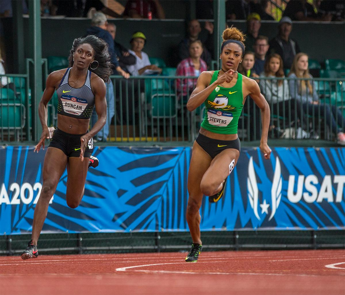 Nike's Kimberlyn Duncan and Oregon's Deajah Stevens race around the corner in the 200 meter semi-finals. Stevens won her heat with a time of 22.91. Photo by August Frank, Oregon News Lab