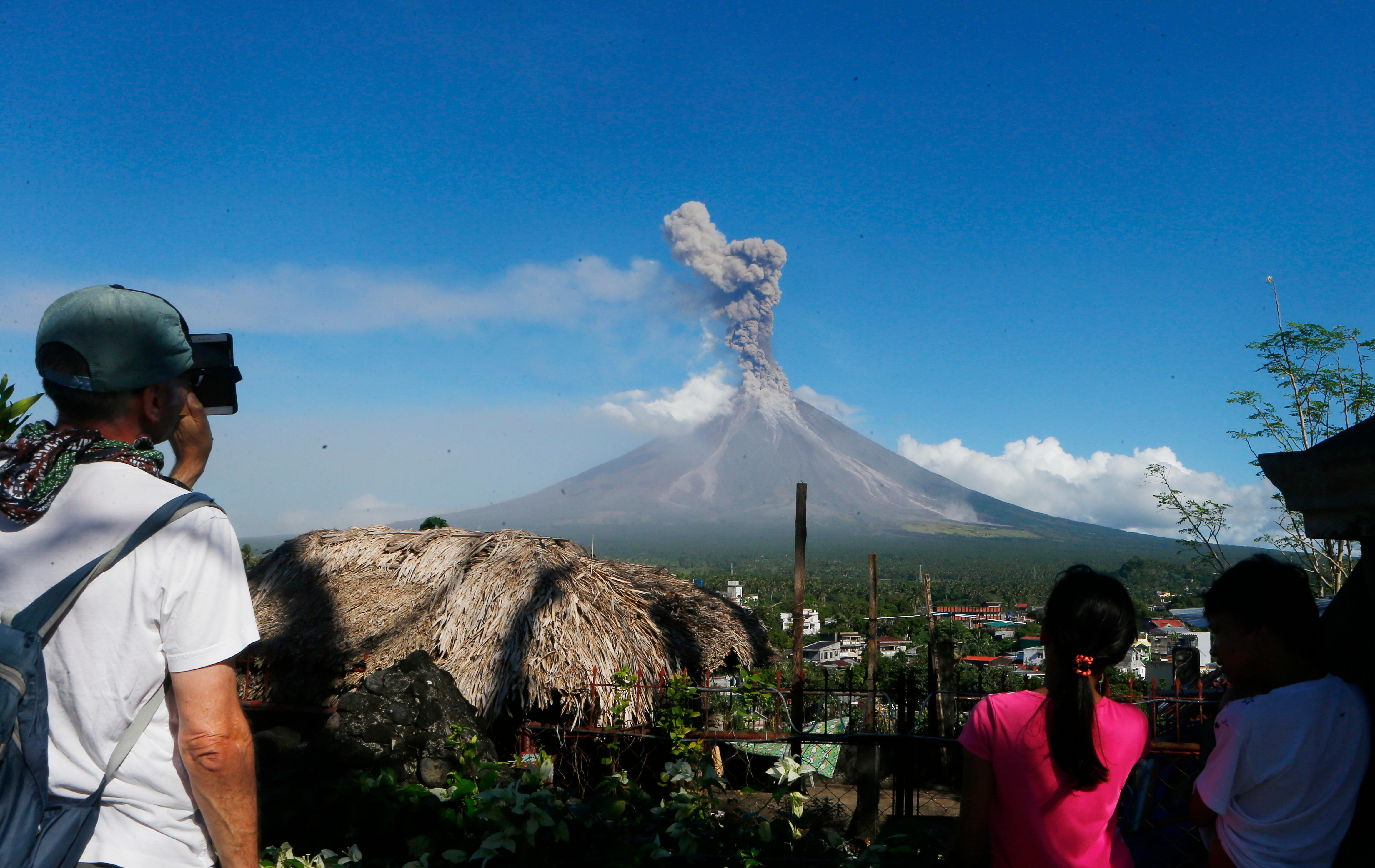 A foreign tourist, left, takes photos of an erupting Mayon volcano Tuesday, Jan. 23, 2018 as seen from Legazpi city, Albay province, southeast of Manila, Philippines. The Philippines' most active volcano ejected a huge column of lava fragments, ash and smoke in another thunderous explosion at dawn Tuesday, sending thousands of villagers back to evacuation centers and prompting a warning that a violent eruption may be imminent. (AP Photo/Bullit Marquez)