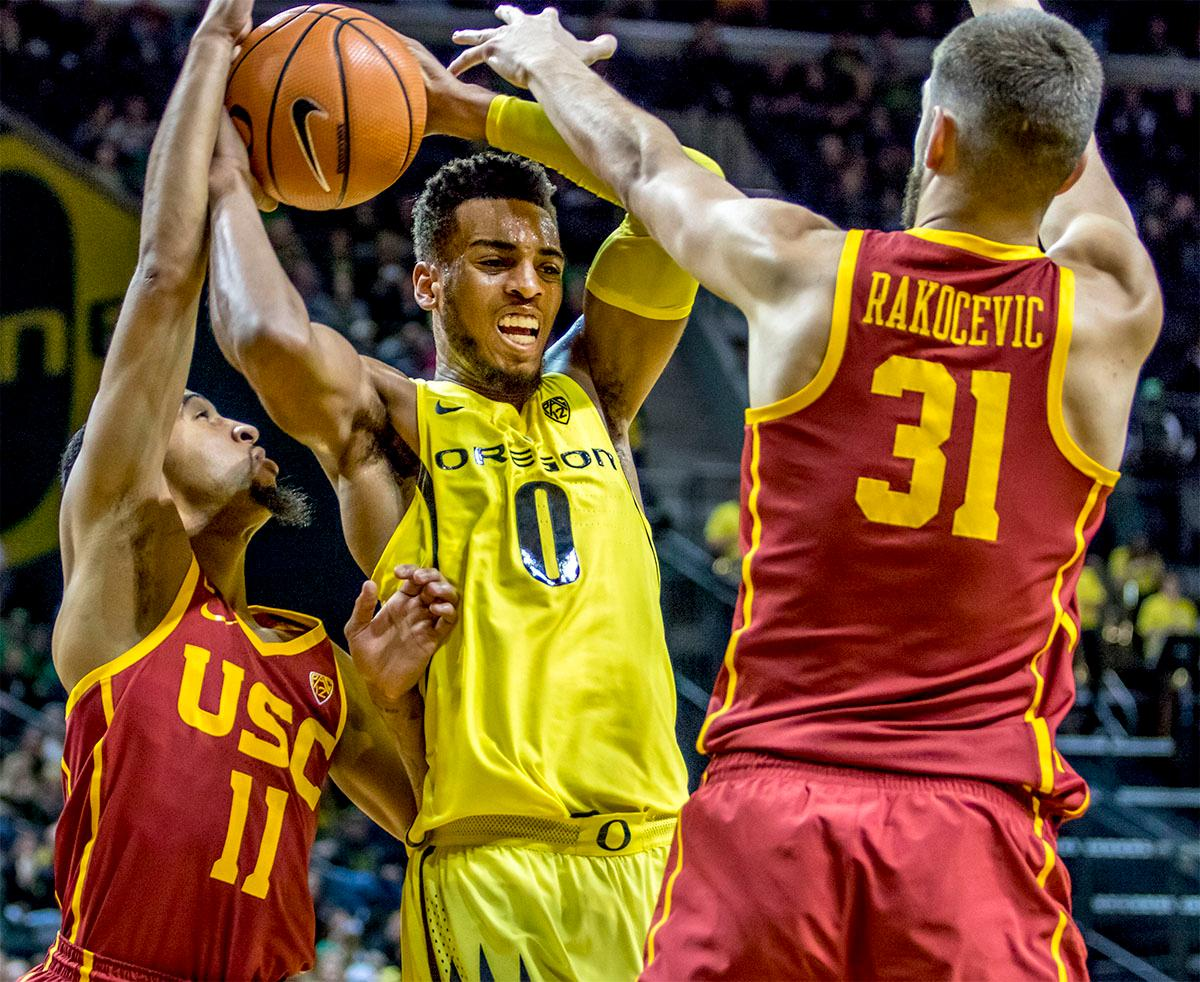 The Duck's Troy Brown Jr. (#0) fights off the Trojan's Jordan McLaughlin (#11) and Nick Rakocevic (#31). The UO Ducks basketball team suffered a loss to the USC Trojans, 75-70, at Matthew Knight Arena on Thursday. Payton Pritchard lead the scoring with 18 points. The Ducks are now 2-4 in conference play and 12-7 overall. The Ducks will next play the UCLA at Matthew Knight Arena at 7:15 p.m. on Saturday, Jan. 20. Photo by August Frank, Oregon News Lab