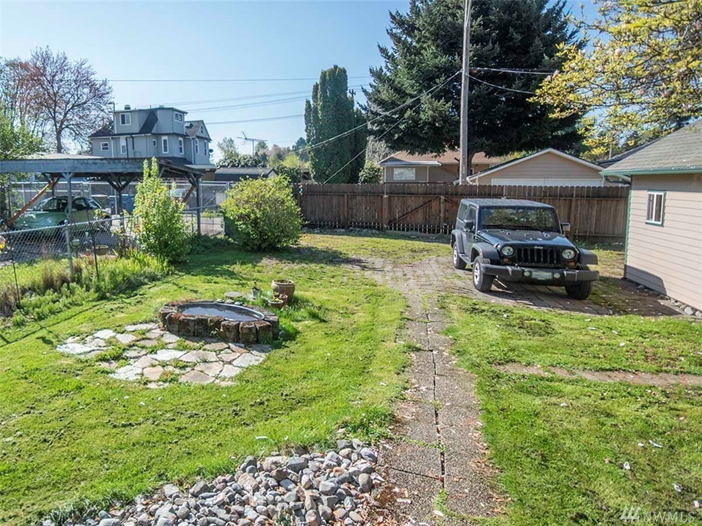The charming home sits on a 6,000 foot level lot and has an kitchen and eating space, laundry area and sliding door that opens to covered deck for a lovely backyard. There is alley access, a new shed for extra storage, and is close to shopping, restaurants and night life (Image courtesy of Keller Williams Great Seattle).