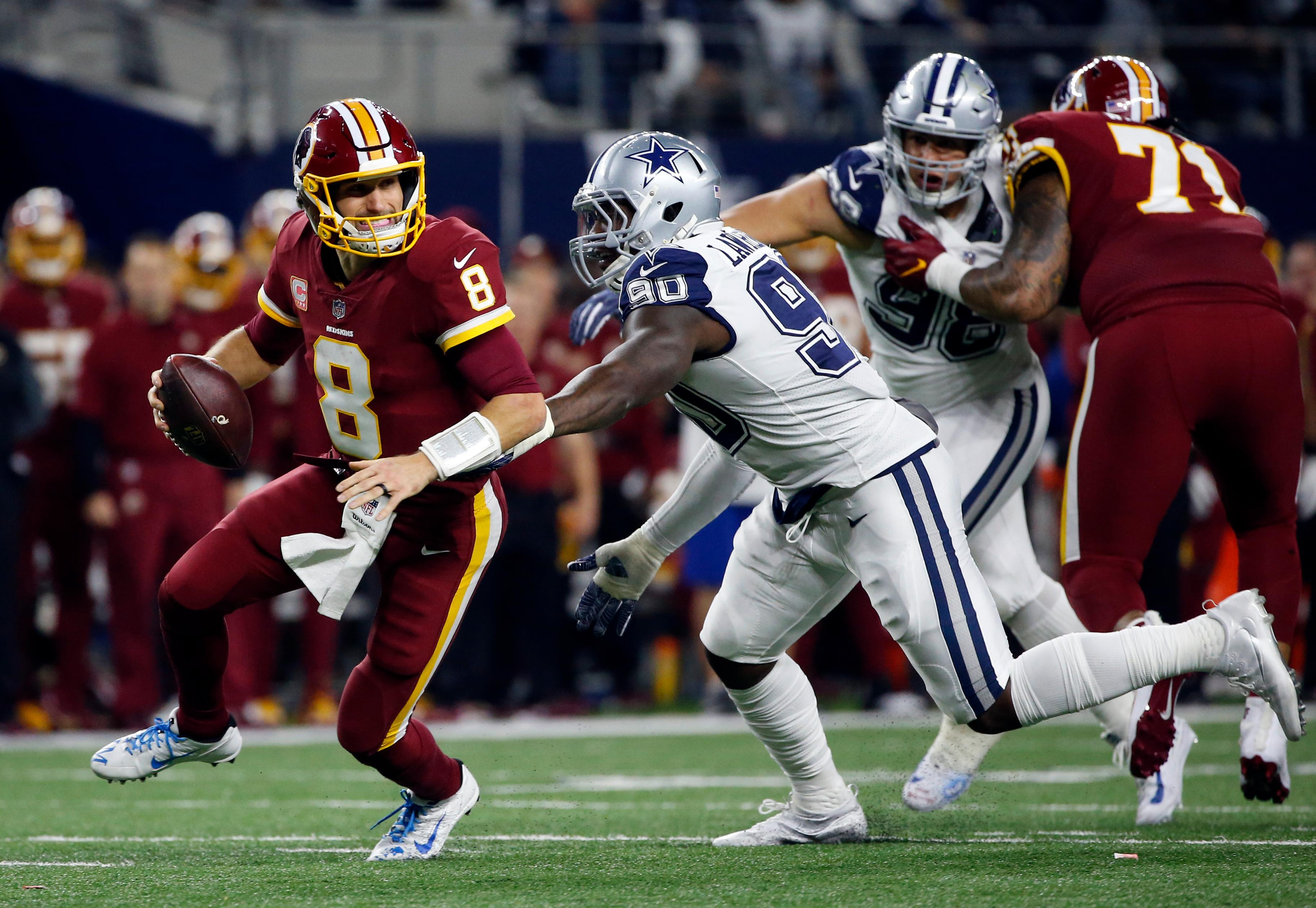 Washington Redskins quarterback Kirk Cousins (8) scrambles out of the pocket escaping pressure from Dallas Cowboys defensive end DeMarcus Lawrence in the first half of an NFL football game, Thursday, Nov. 30, 2017, in Arlington, Texas. (AP Photo/Ron Jenkins)