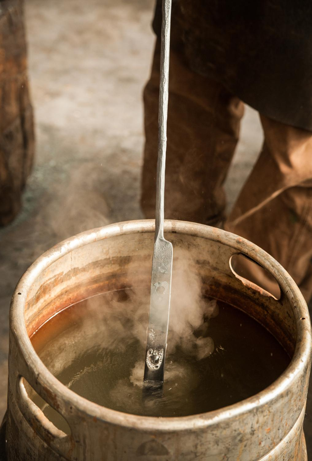 "Inside his Essex studio in Walnut Hills, artist-blacksmith Mark Gilsdorf dips a scalding hot piece of steel in a ""quench bucket"" to lower the temperature of the metal. He's making fireplace tongs, part of a commissioned set of tools. / Image: Melissa Doss Sliney"