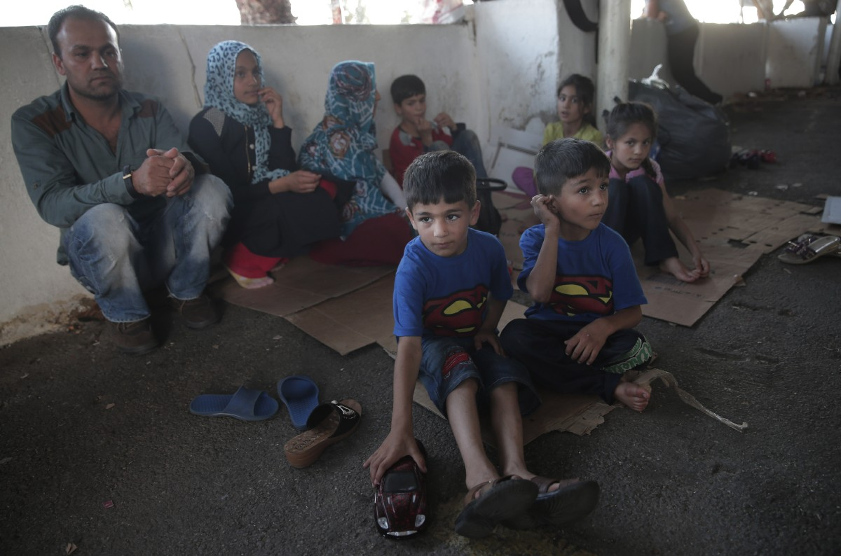 Migrant brothers Youssef Ahmed Zaid, 5, center, and three and a half year old Muslim Ahmed Zeid, right, from Afghanistan, along with the rest of the family, sit at the bus station where they have sought shelter until they can cross into Greece, in the coastal town of Bodrum, Turkey, Sunday, Aug. 16, 2015. The city of Bodrum, a magnet for wealthy tourists, is these days drawing plenty of other visitorsó migrants fleeing conflicts in the Middle East and Africa and seeking a better life in Europe. At its closest point, the Greek island of Kos is only 4 kilometers (2.5 miles) from Turkey and migrants, mostly from Syria, but also from Afghanistan, Iran and African nations often try to cross in groups upward of eight people in small inflatable plastic boats meant for a maximum of four, powered by tiny electric outboard motors and plastic paddles. (AP Photo/Lefteris Pitarakis)