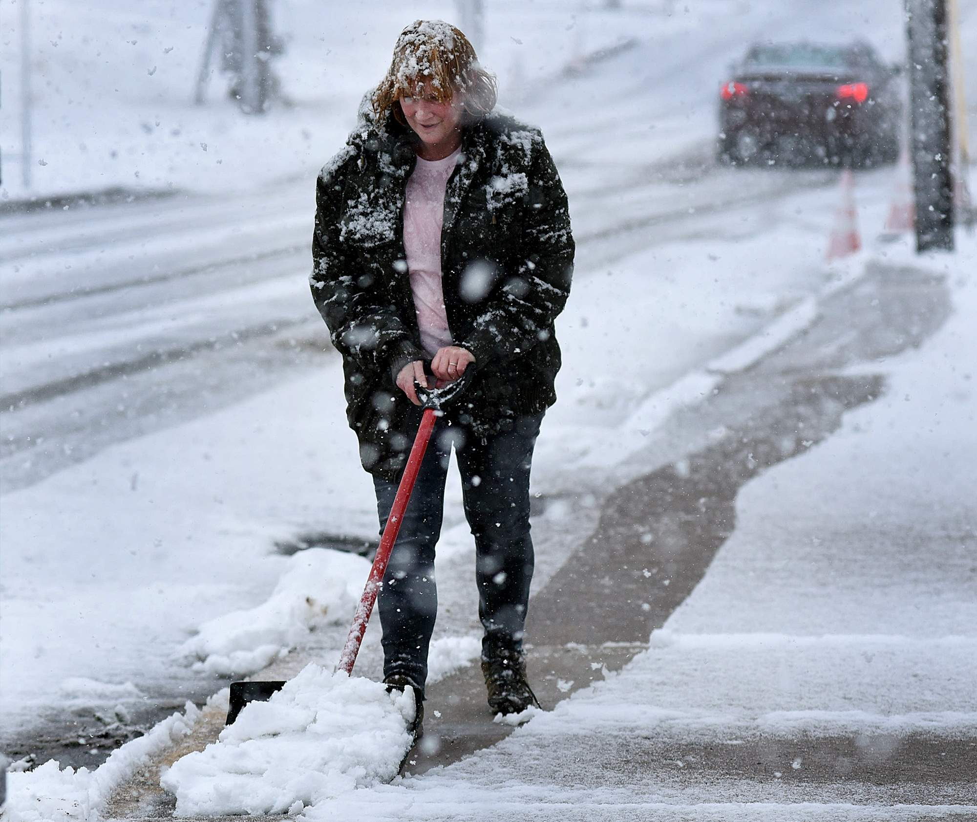 Lisa Ferketich shovels the sidewalk in front of her place of business on Reliance Rd in Souderton during the second snow storm to hit the area in the past week. [ART GENTILE / STAFF PHOTOJOURNALIST]