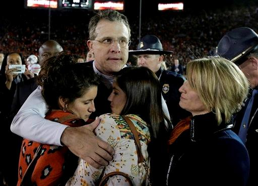 Auburn head coach Gus Malzahn is hugged following the NCAA BCS National Championship college football game against Florida State Monday, Jan. 6, 2014, in Pasadena, Calif. Florida State won 34-31.