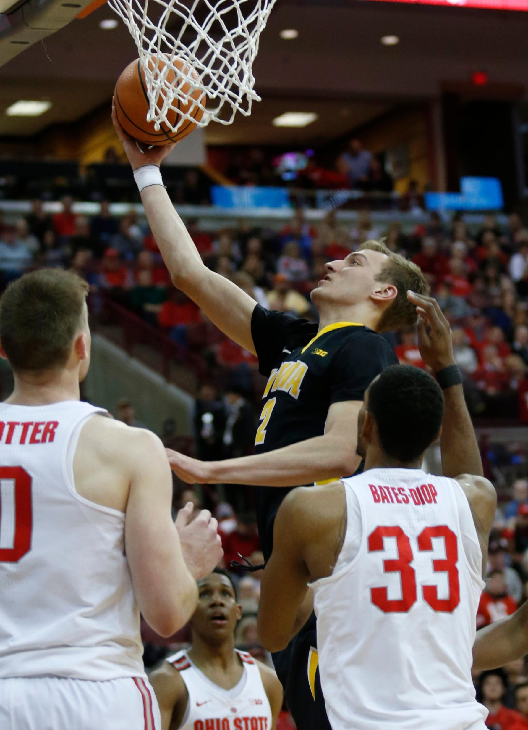 Iowa forward Jack Nunge, center, goes up for a shot between Ohio State center Micah Potter, left, and forward Keita Bates-Diop during the first half of an NCAA college basketball game in Columbus, Ohio, Saturday, Feb. 10, 2018. (AP Photo/Paul Vernon)