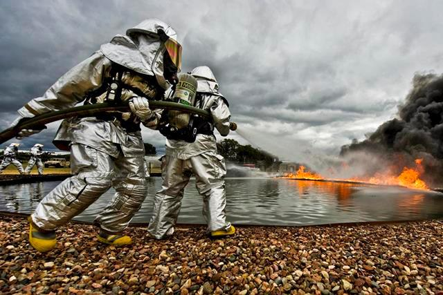 Firefighters maneuver a hose to attack fires to support Warrior and Global Medic exercises on Fort McCoy, Wis., July 27, 2013. The Exercise enables units to rehearse military maneuvers and tactics.