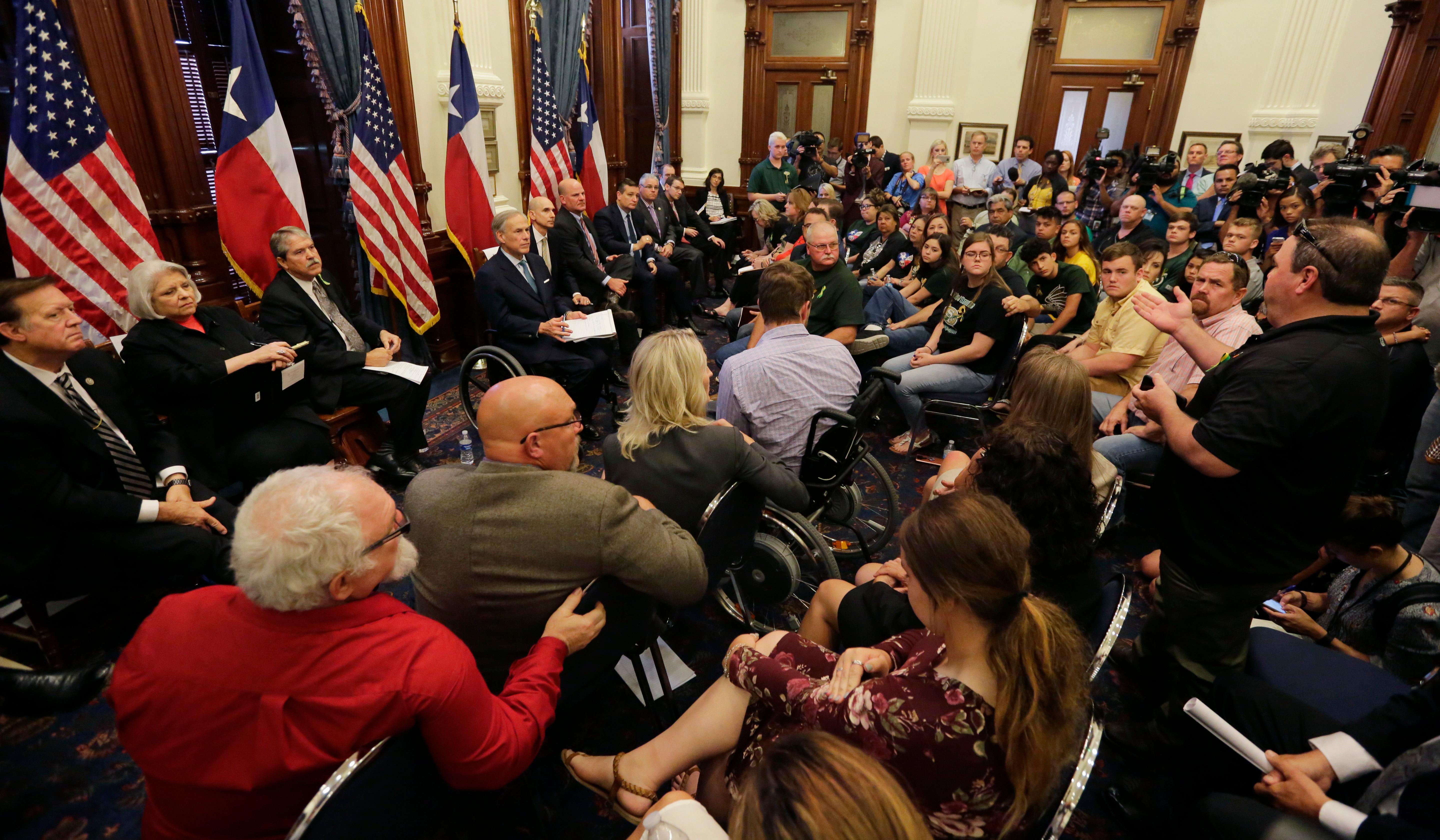 Scot Rice, standing right, speaks during a roundtable discussion in Austin, Texas, Thursday, May 24, 2018, hosted by Texas Gov. Gregg Abbott to address safety and security at Texas schools in the wake of the shooting at Santa Fe, Texas. Rice's wife Flo Rice, a substitute teacher, was carried from the Santa Fe scene of last week's school shooting after she was shot in the leg. (AP Photo/Eric Gay)