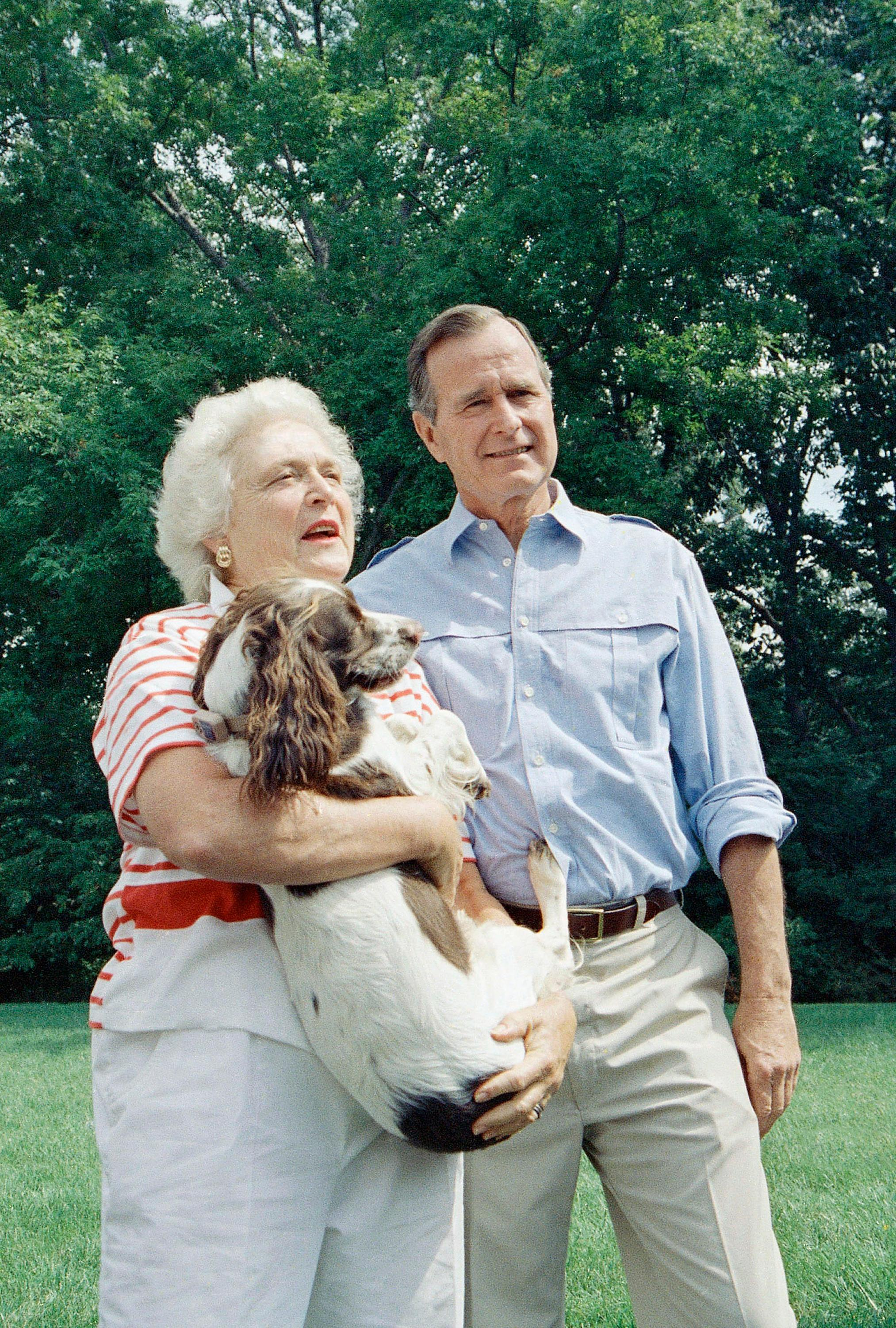"FILE - In this Sept. 3, 1988 file photo, Vice President George H.W. Bush, right, and his Barbara Bush, holding the family dog, talk to reporters after a press conference outside their home in Washington, D.C. Former first couple George and Barbara Bush's relationship is a true love story, described by granddaughter Jenna Bush Hager as ""remarkable."" They met at a Christmas dance. She was 17. He was 18. Two years later they were married. Now 73 years later, with Barbara Bush declining further medical care for health problems, they are the longest-married couple in presidential history. (AP Photo/J. Scott Applewhite, File)"