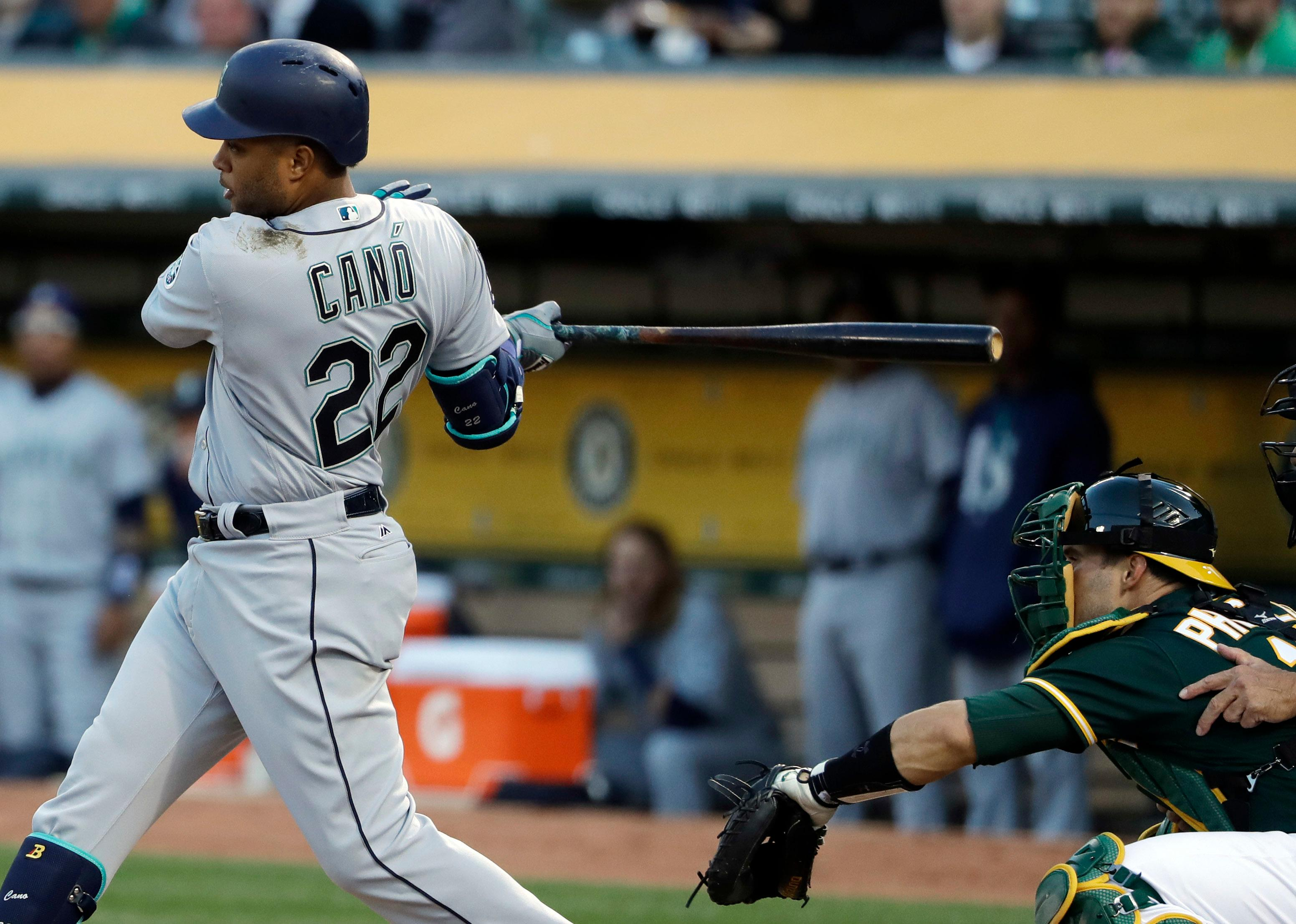 Seattle Mariners' Robinson Cano (22) drives in a run with a single against the Oakland Athletics during the first inning of a baseball game Thursday, April 20, 2017, in Oakland, Calif. (AP Photo/Marcio Jose Sanchez)