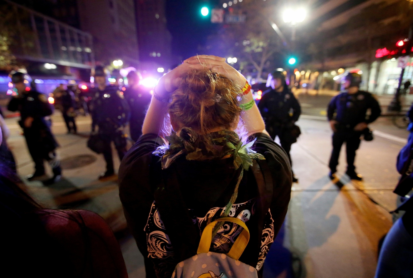 A protester faces a police line in downtown Oakland, Calif., early Wednesday, Nov. 9, 2016. President-elect Donald Trump's victory set off multiple protests. (Jane Tyska/Bay Area News Group via AP)