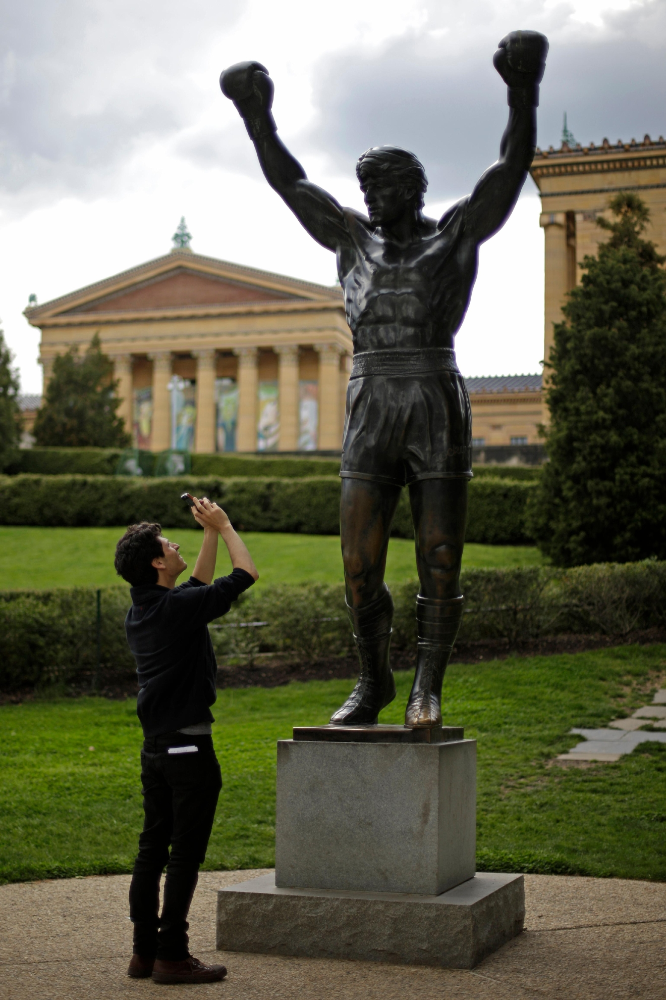 "FILE – In this May 8, 2013, file photo, a tourist photographs a statue of the movie character Rocky Balboa outside the Philadelphia Museum of Art in Philadelphia. Four decades after the Nov. 21, 1976, premiere of ""Rocky,"" the movie's reach is international, and the title character's underdog tale of determination, grit and sleepy-eyed charm still resonates with fans. (AP Photo/Matt Rourke, File)"