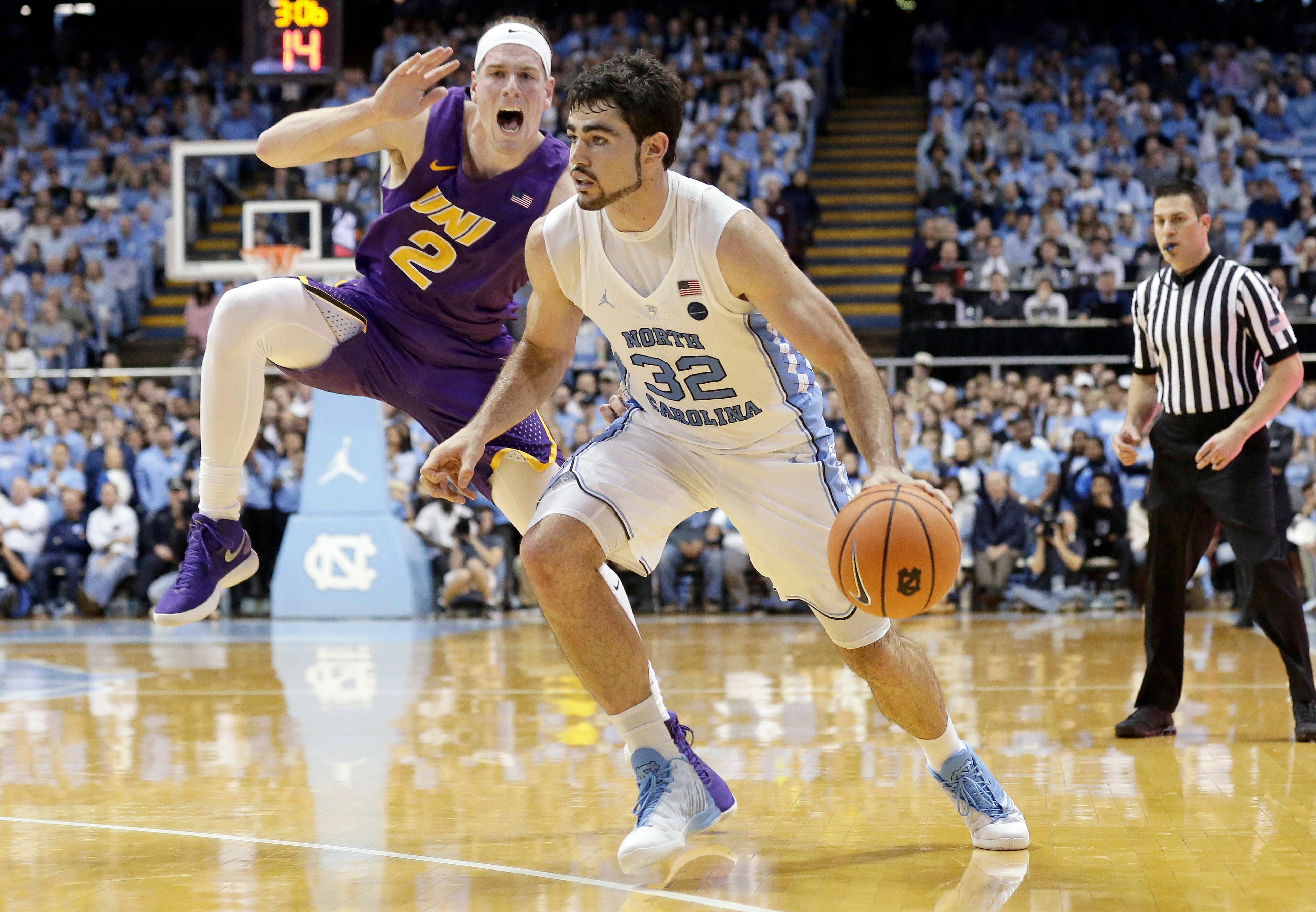 North Carolina's Luke Maye (32) dribbles while Northern Iowa's Klint Carlson (2) defends during the first half of an NCAA college basketball game in Chapel Hill, N.C., Friday, Nov. 10, 2017. (AP Photo/Gerry Broome)