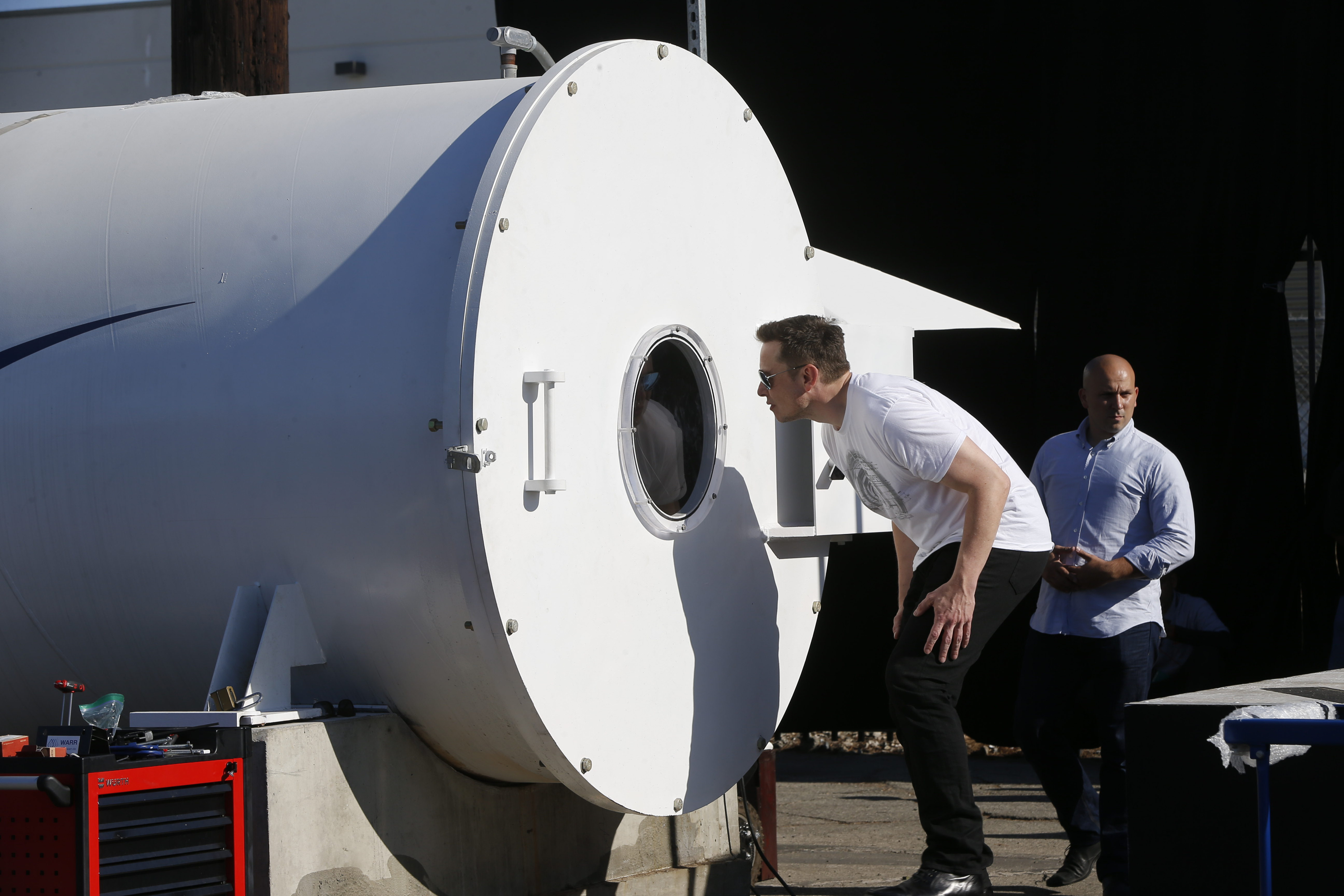 Telsa CEO Elon Musk peaks inside the Hyperloop track door at the Hyperloop Pod Competition II at SpaceX's Hyperloop track in Hawthorne, Calif., Sunday, Aug. 27, 2017. The Hyperloop system built by SpaceX is approximately one mile in length with a six-foot outer diameter. The WARR team from Tech University Munich won the Hyperloop Pod Competition II with a peak speed of 324 kilometers per hour (201 mph). (AP Photo/Damian Dovarganes)