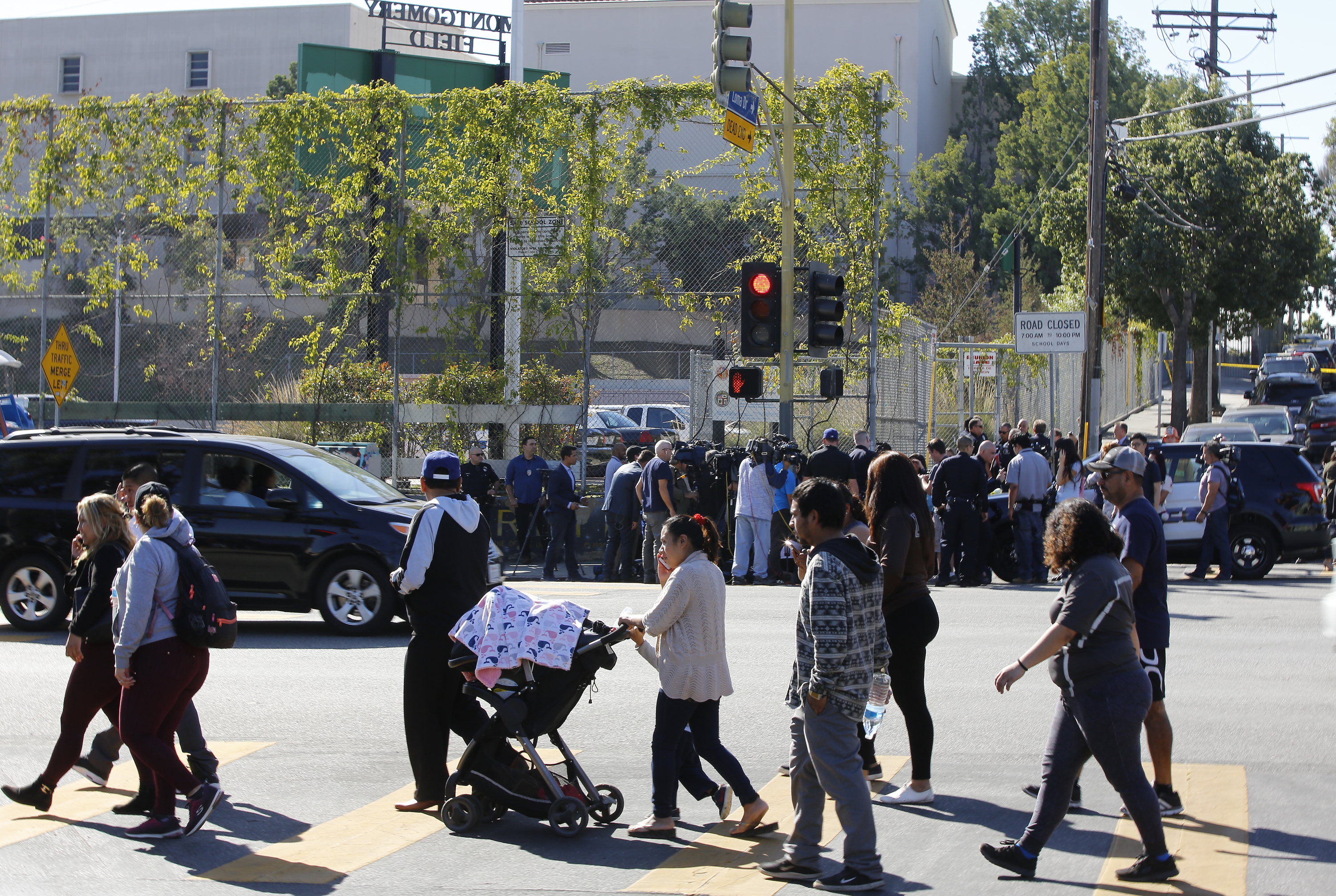 Parents waiting for news of their children are asked by school authorities to wait across the cordoned off the Belmont High School in Los Angeles Thursday, Feb. 1, 2018. Two students were shot and wounded, one critically, inside a Los Angeles middle school classroom Thursday morning and police arrested a female student believed to be 12 years old, authorities said. (AP Photo/Damian Dovarganes)
