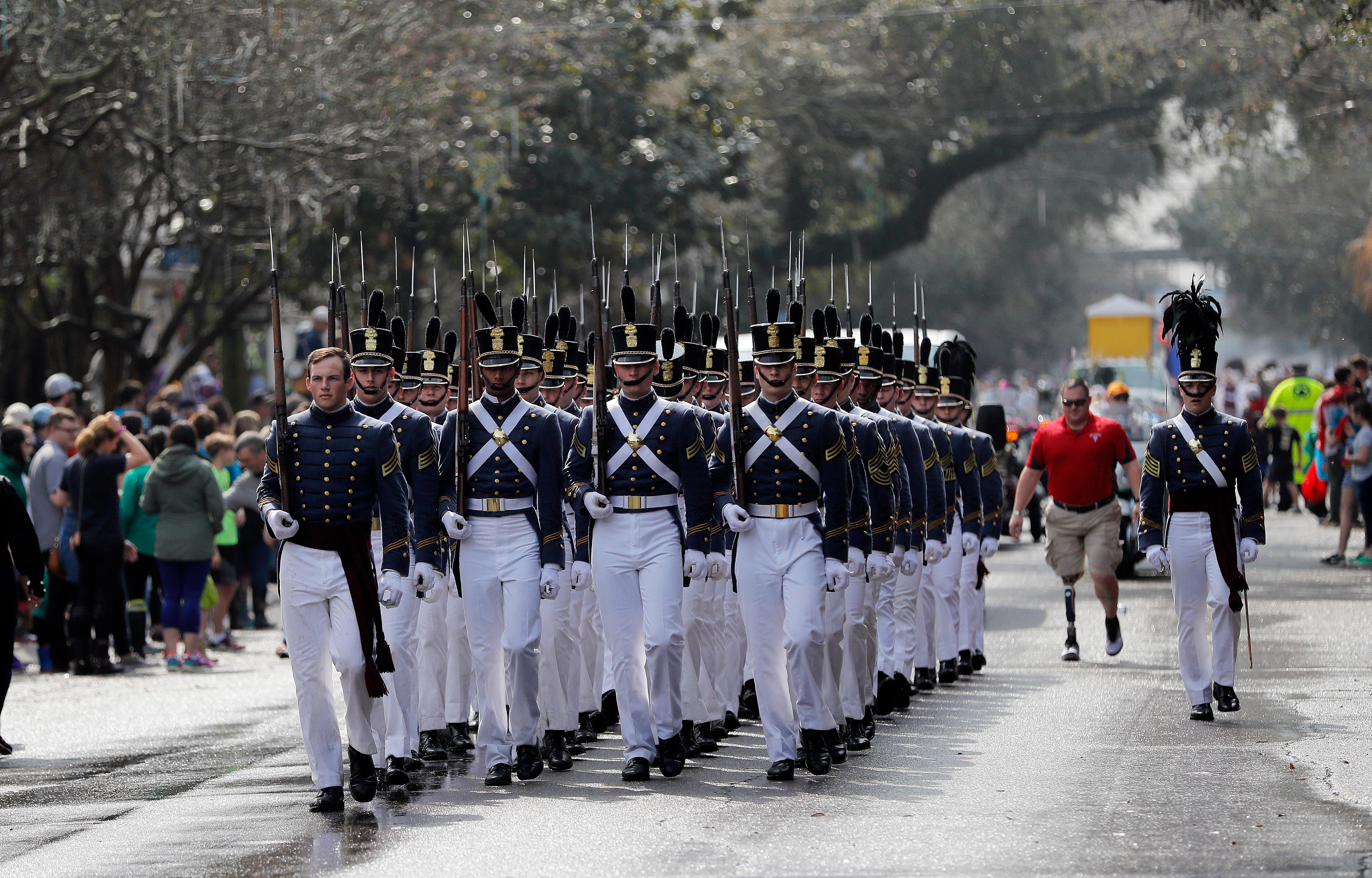 A military drill team marches during the Krewe of Thoth Mardi Gras parade in New Orleans, Sunday, Feb. 11, 2018. The krewe's original parade route was designed specifically to serve people who were unable to attend other parades in the city. The route passes in front of several extended healthcare facilities. Carnival season will culminate on Mardi Gras day this Tuesday, Feb. 13. (AP Photo/Gerald Herbert)