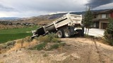 Dump truck slides down embankment, nearly lands on golf course in west Reno