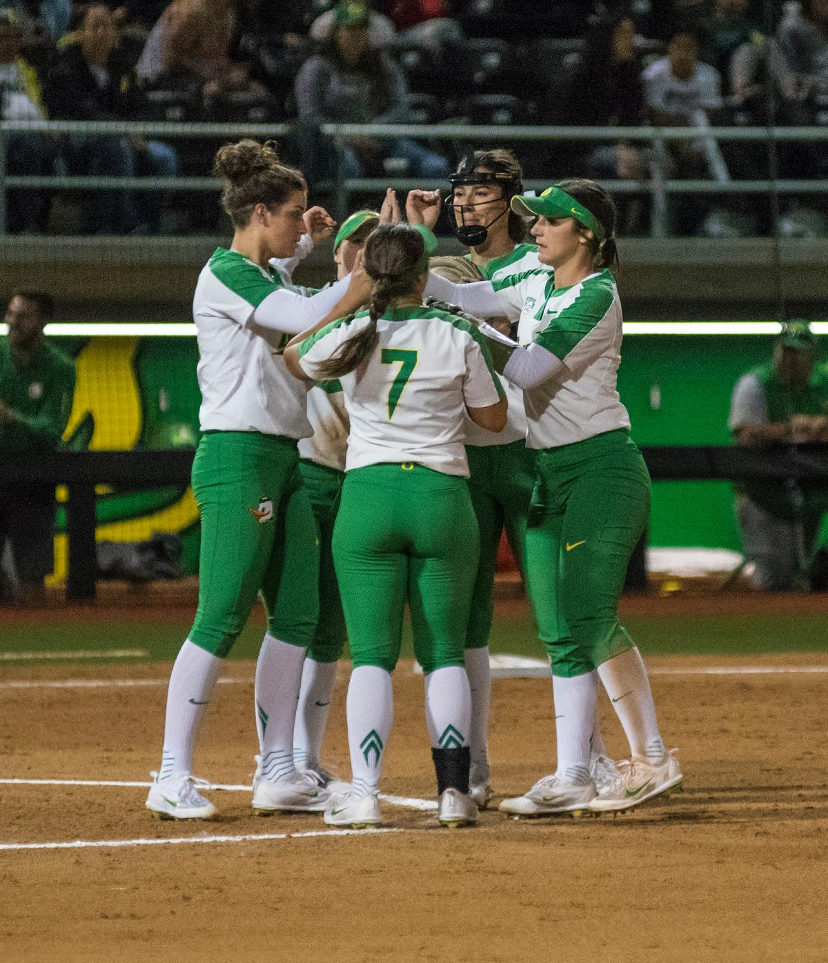 The Oregon Ducks teammates high five after a time out. The No. 3 Oregon Ducks defeated the University of Illinois Chicago Flames 13-0 with the run-rule on Saturday night at Jane Sanders Stadium. The Ducks scored in every inning and then scored nine runs at the bottom of the fourth. The Oregon Ducks are now 22-0 in NCAA regional games. The Oregon Ducks play Wisconsin next on Saturday, May 20 at 2pm at Jane Sanders Stadium. Photo by Cheyenne Thorpe, Oregon News Lab