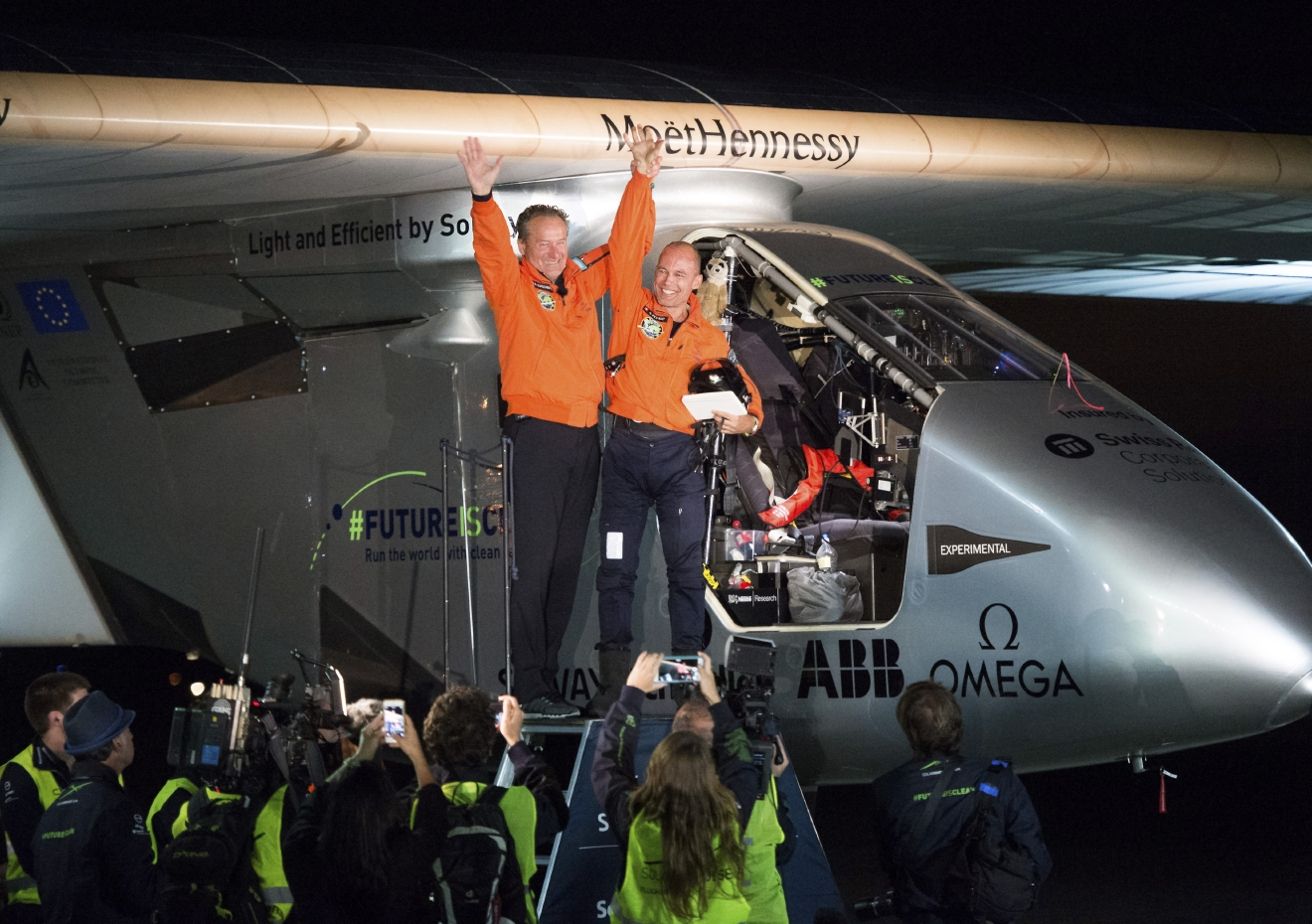 Solar Impulse 2 pilots Bertrand Piccard, right, and Andre Borschberg celebrate after Piccard landed their solar-powered plane at Moffett Field in Mountain View, Calif.,  on Saturday, April 23, 2016. The solar-powered airplane landed in California on Saturday, completing a risky, three-day flight across the Pacific Ocean as part of its journey around the world. (AP Photo/Noah Berger)
