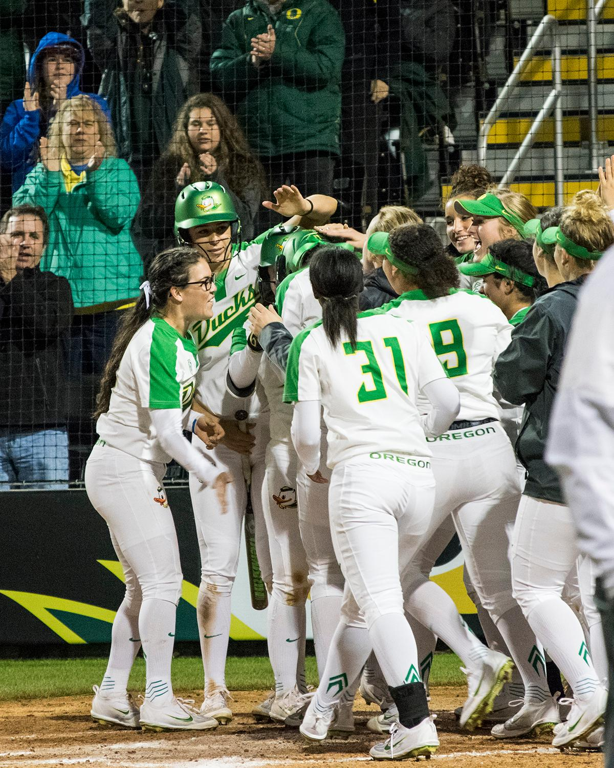Oregon Ducks players celebrate Oregon Duck catcher Gwen Svekis (#21) solo home run.In the first of a three game series the Oregon Ducks defeated the California Golden Bears five to one. Photo by Kezia Setyawan, Oregon News Lab