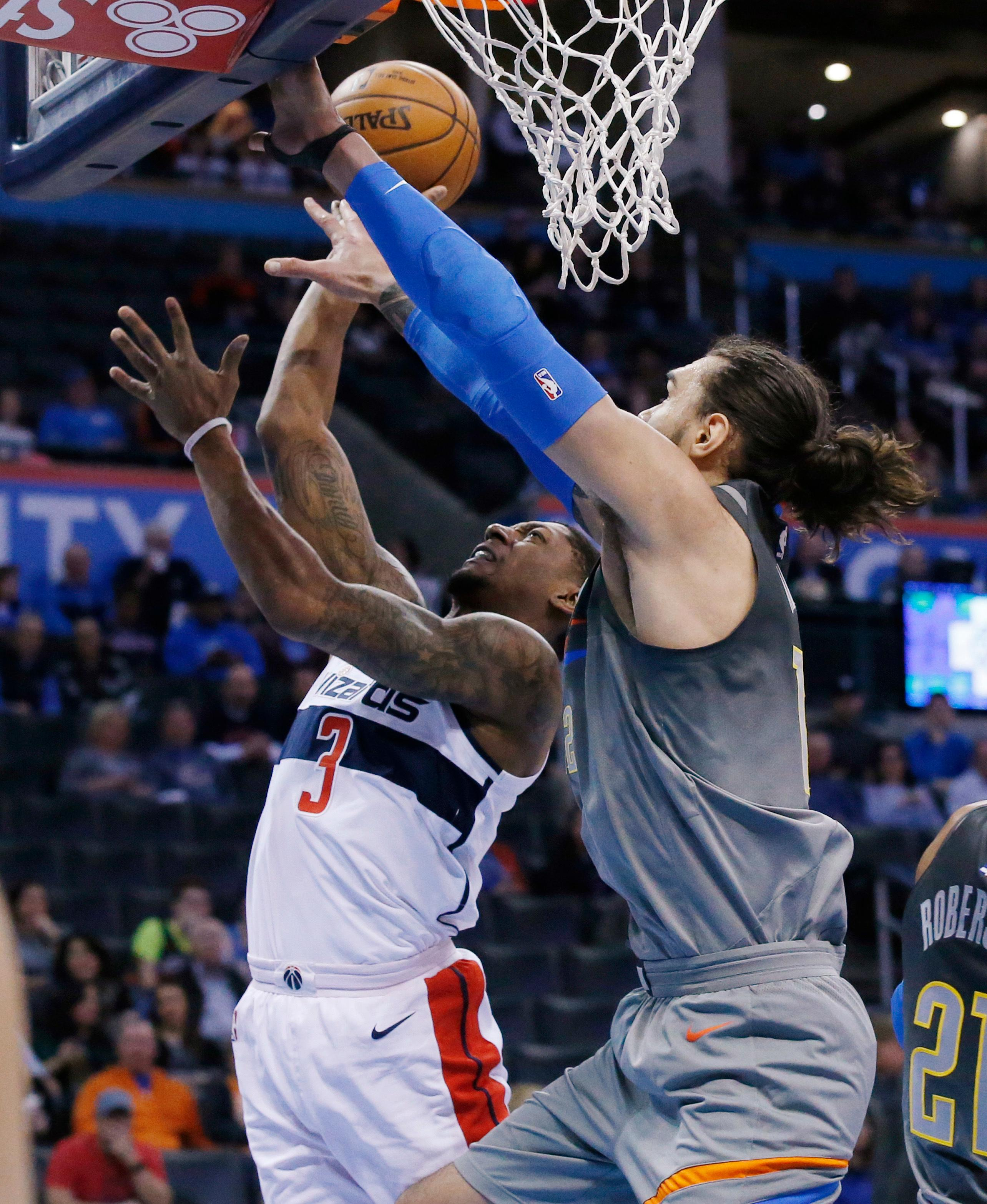 Washington Wizards guard Bradley Beal (3) shoots as Oklahoma City Thunder center Steven Adams, right, defends during the first quarter of an NBA basketball game in Oklahoma City, Thursday, Jan. 25, 2018. (AP Photo/Sue Ogrocki)