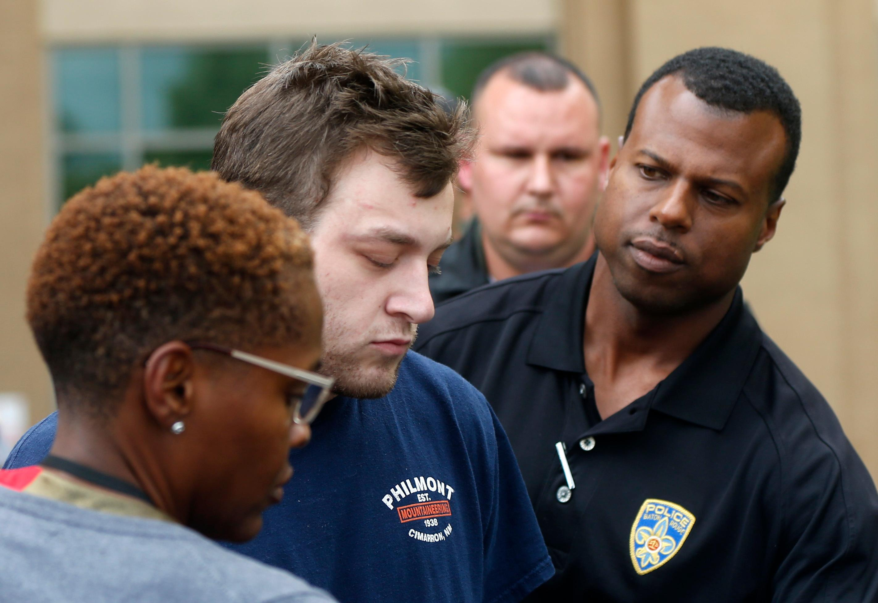 Kenneth James Gleason is escorted by police to a waiting police car in Baton Rouge, La., Tuesday, Sept. 19, 2017. Gleason is charged with two counts of first degree murder and other charges, for three shootings in the Baton Rouge area throughout the past week that resulted in the death of two men. (AP Photo/Gerald Herbert)