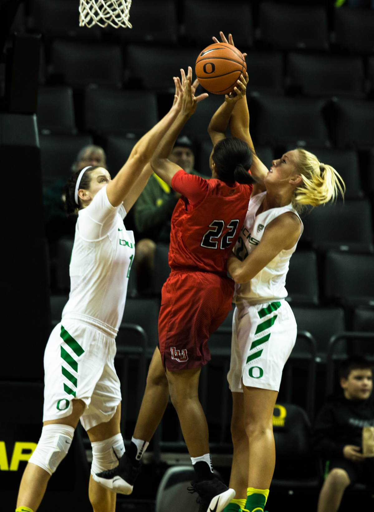 Lamar Cardinal's guard DeA'ngela Mathis (#22) attemps a lay up while Ducks forwards Jacina Vandenberg (#15) and Lauren Yearwood (#22) attempt to block.  The Oregon Ducks women's basketball team won their season opener against the Lamar Cardinals 84-67.  Photo by Austin Hicks, Oregon News Lab