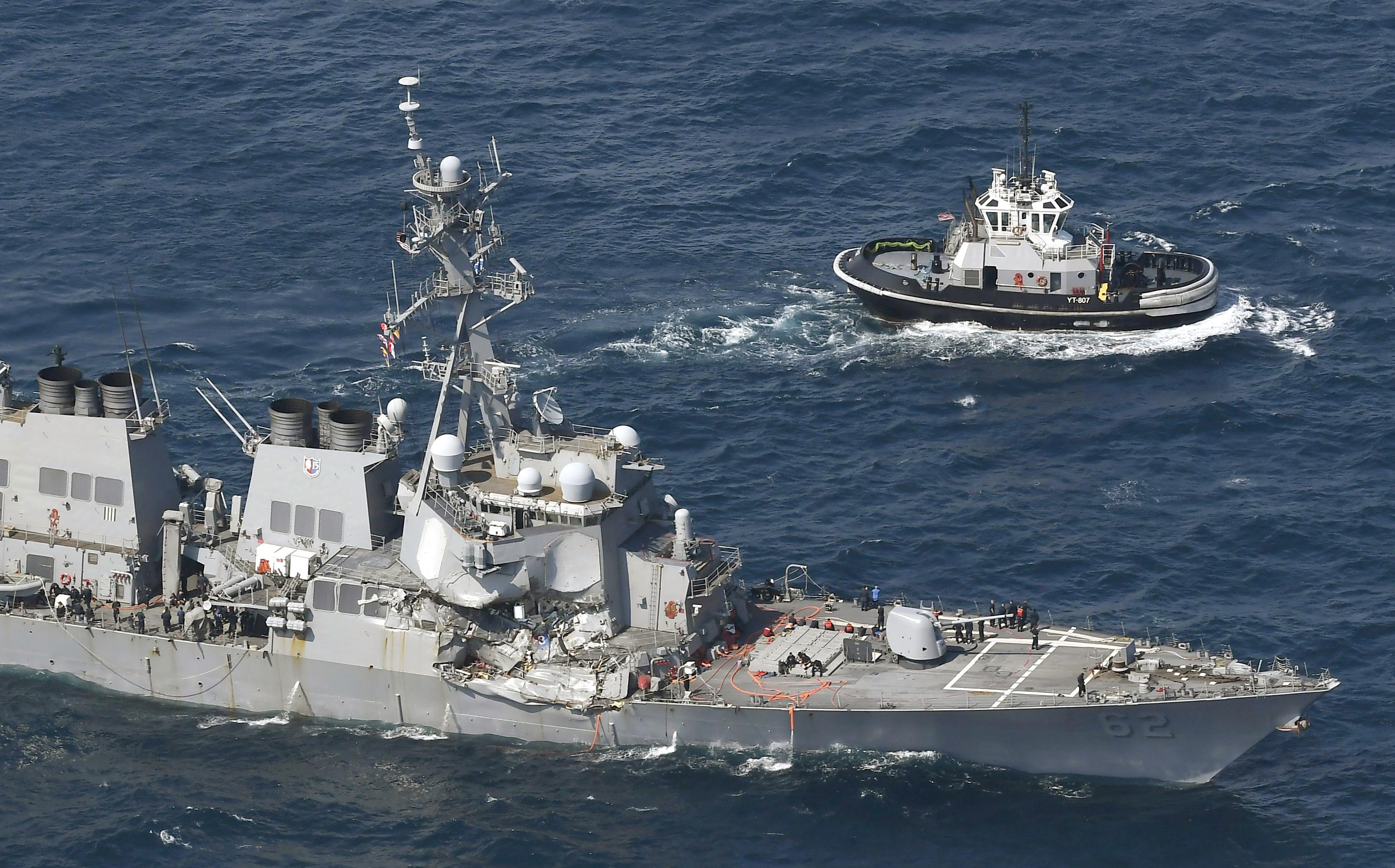 The USS Fitzgerald, left, heads to Yokosuka, home base of the 7th Fleet,  beside a U.S. tugboat, off Shimoda, Shizuoka prefecture, Japan, after the Navy destroyer collided with a merchant ship, Saturday,  June 17, 2017.  The U.S. Navy says the USS Fitzgerald suffered damage below the water line on its starboard side after it collided with a Philippine-flagged merchant ship.  (Iori Sagisawa/Kyodo News via AP)