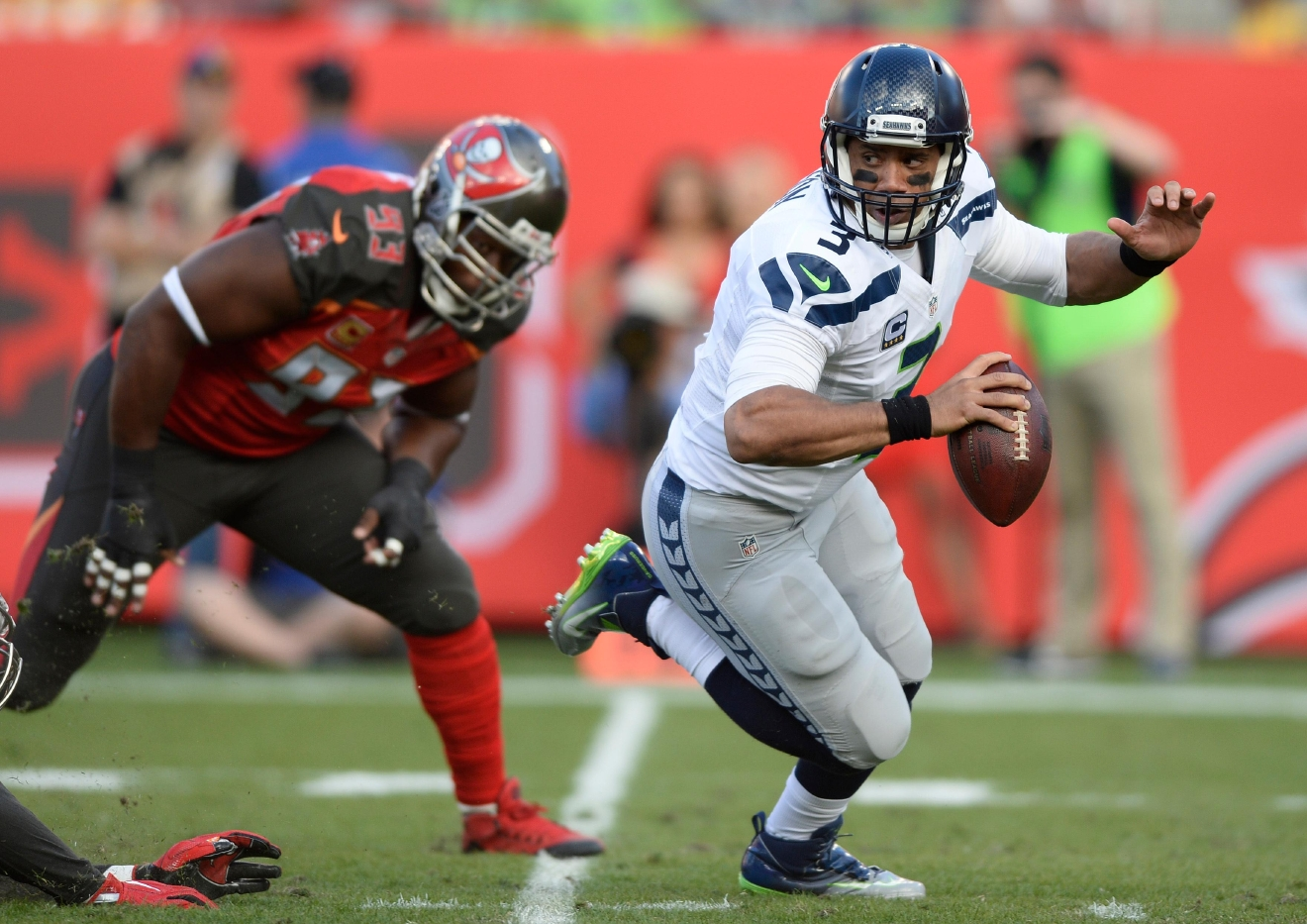 Seattle Seahawks quarterback Russell Wilson (3) scrambles away from Tampa Bay Buccaneers defensive tackle Gerald McCoy (93) during the first quarter of an NFL football game Sunday, Nov. 27, 2016, in Tampa, Fla. (AP Photo/Jason Behnken)