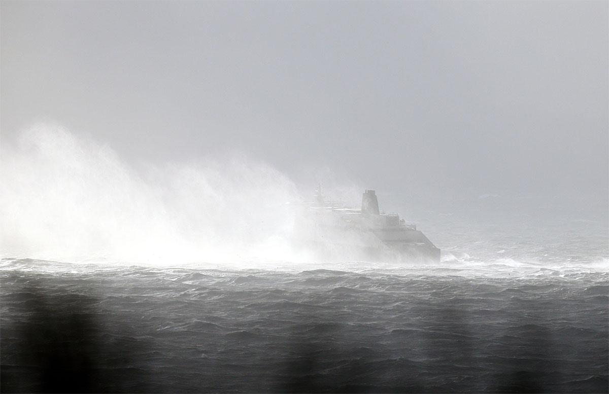 Waves crash into a ferry off the coast of Dover, south east England, as a storm, Storm Angus, the year's first big winter storm in Britain, lashes England's south coast, Sunday Nov. 20, 2016. Forecasters say winds of 68 mph (110 kph) hit the south coast early Sunday, with a gust of 97 mph (156 kph) recorded offshore. (Gareth Fuller/PA via AP)