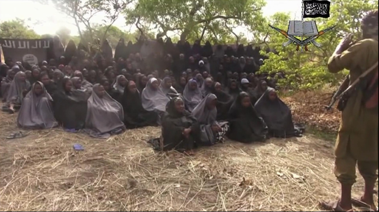 This May 12, 2014, file image taken from video posted by Nigeria's Boko Haram terrorist network purports to show the missing girls abducted from a boarding school in the northeastern town of Chibok. Soldiers have found one of the kidnapped girls, her uncle said Wednesday, May 18, 2016 describing her as pregnant and traumatized but otherwise fine. (Militant Video via AP, File)