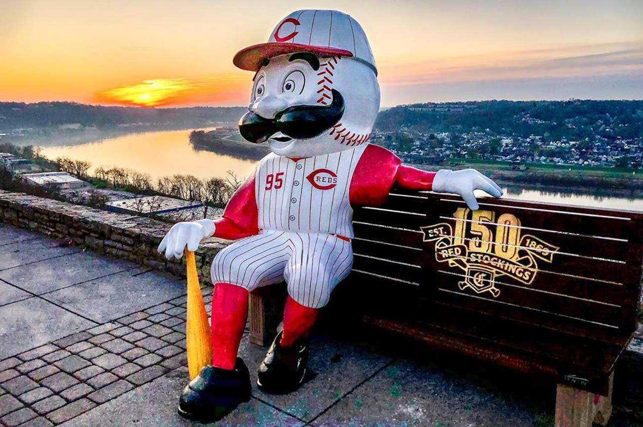 To celebrate the Reds' 150th Anniversary, 24 benches featuring Mr. Redlegs sculptures have been added to various spots around the area, as well as out of town locations including Dayton, Loveland, and Louisville, for the perfect Reds photo op. The mascot sports different uniforms from throughout the team's history at each of the benches. The Reds have been wearing these same throwback uniforms during their 2019 season. / Location: Twin Lakes Overlook at Eden Park / Uniform: 1995 / Image courtesy of Instagram user @photogdslavey   // Published: 5.14.19