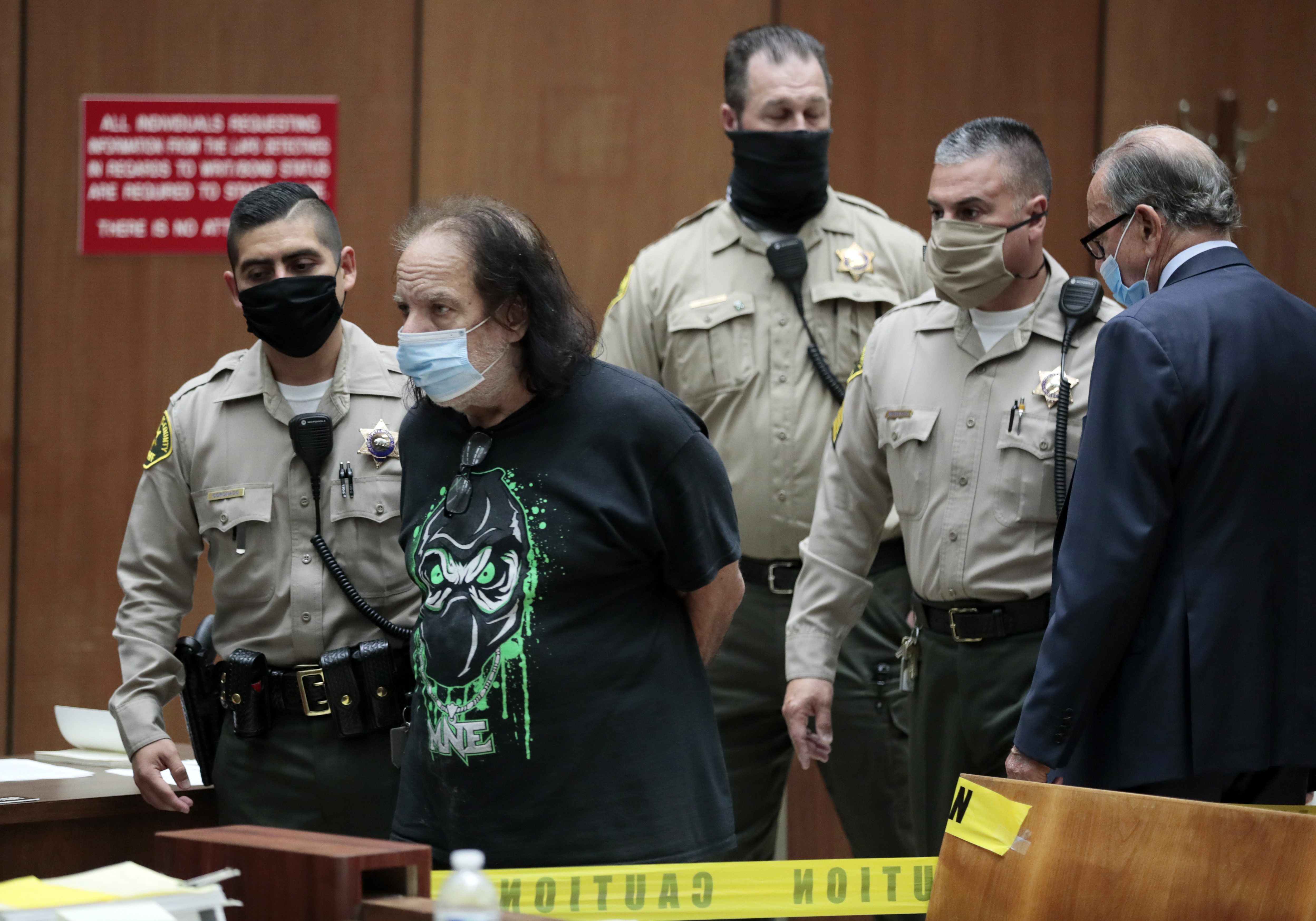 Adult film star Ron Jeremy, second left, appears in court with his attorney Stuart Goldfarb, right, upon being charged with sexually assaulting four women, in Dept. 30 at Los Angeles Superior Court in Los Angeles, Tuesday, June 23, 2020. Los Angeles County prosecutors say Jeremy has been charged with raping three women and sexually assaulting a fourth. (Robert Gauthier/Los Angeles Times via AP, Pool)