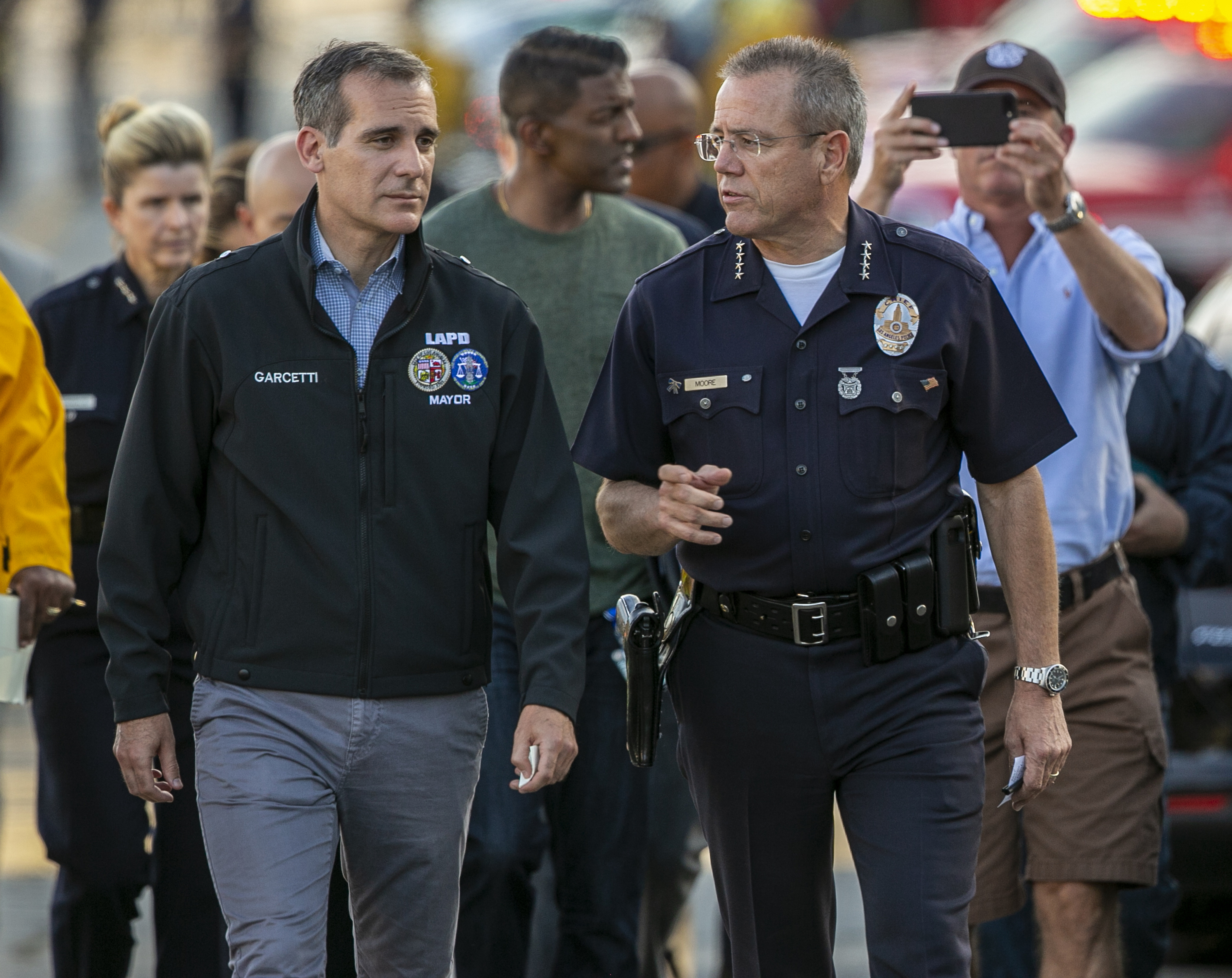 Los Angeles Mayor Eric Garcetti, left, and Police Chief Michel Moore walk to a news conference after a gunman, who barricaded himself inside a Trader Joe's store, was arrested in Los Angeles Saturday, July 21, 2018. Police believe a man involved in a standoff at the Los Angeles supermarket shot his grandmother and girlfriend and then fired at officers during a pursuit before he crashed into a utility pole outside the supermarket and ran inside the store. Hours after he took hostages in the store, the suspect surrendered.(AP Photo/Damian Dovarganes)