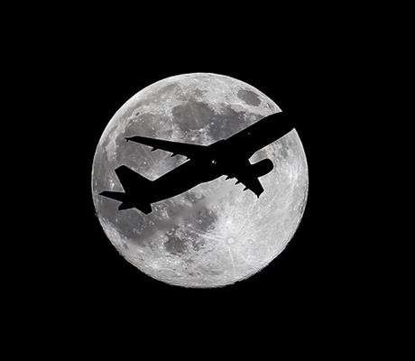 "One day before a ""supermoon,"" Virgin America flight VX415 from New York (JFK) to Los Angeles (LAX) crosses the waxing gibbous moon on its final approach to Los Angeles Airport as viewed from Whittier, Calif., Friday, July 11, 2014."