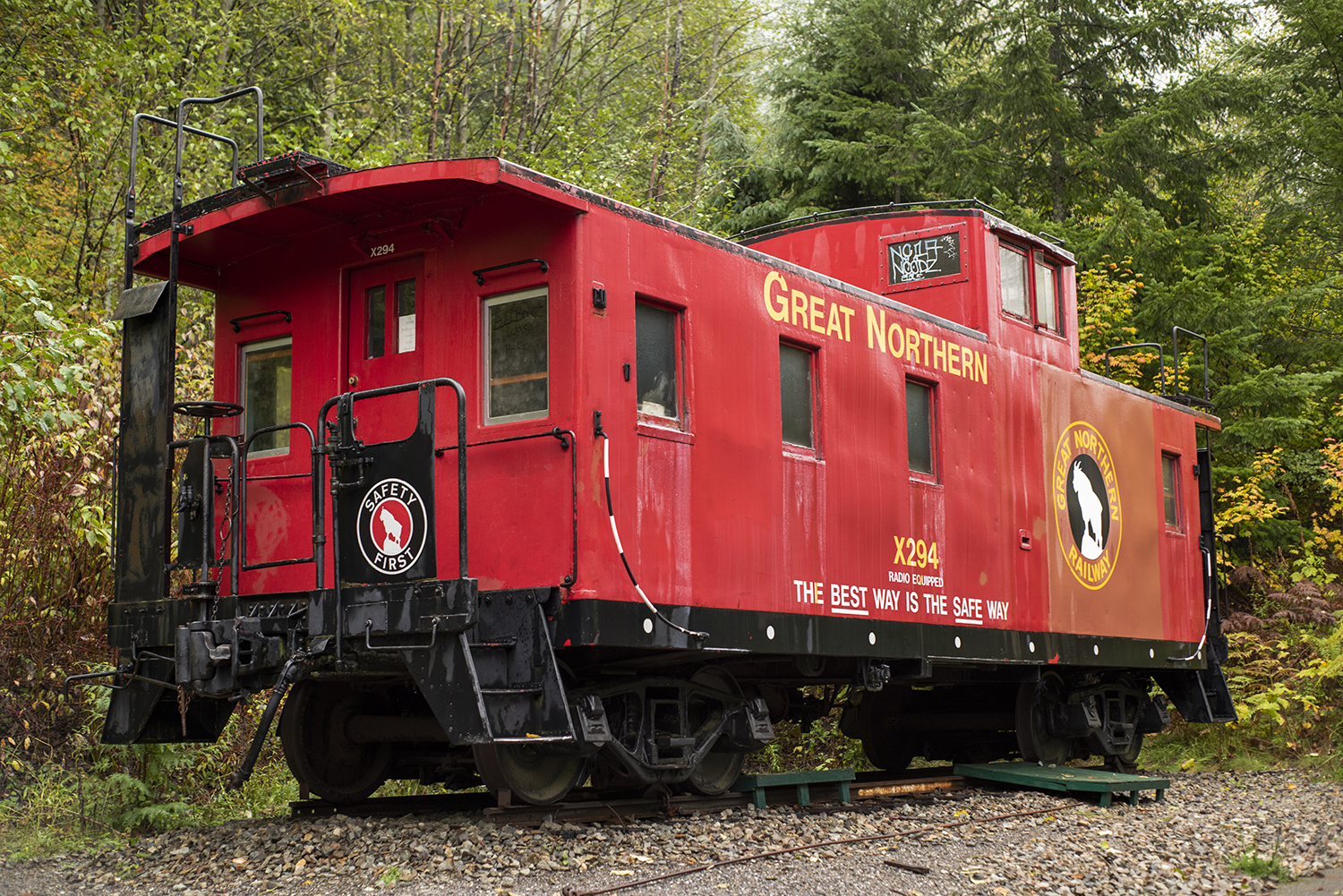 A bright red caboose sits at the trailhead of Iron Goat Trail, right near a paved path that is also ADA-accessible for nearly three miles. And the trail name? It comes from the mountain goat on the Great Northern Railway logo.{ }(Image: Rachael Jones / Seattle Refined)