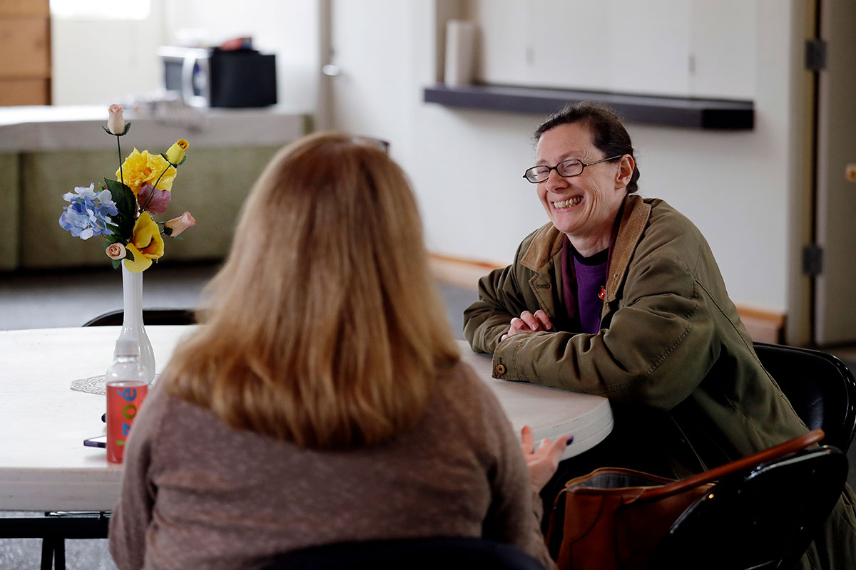 In this Monday, March 5, 2018, photo, Karina O'Malley, right, who helps manage a car camp for homeless people in the parking lot of Lake Washington United Methodist Church, talks with another volunteer in a day room used by the women, in Kirkland, Wash. Some of the obstacles faced by the women in finding permanent housing may soon become illegal in Washington state, where legislators are advancing a bill that would prohibit landlords from turning away tenants who rely on Section 8 vouchers, Social Security or veterans benefits. (AP Photo/Elaine Thompson)