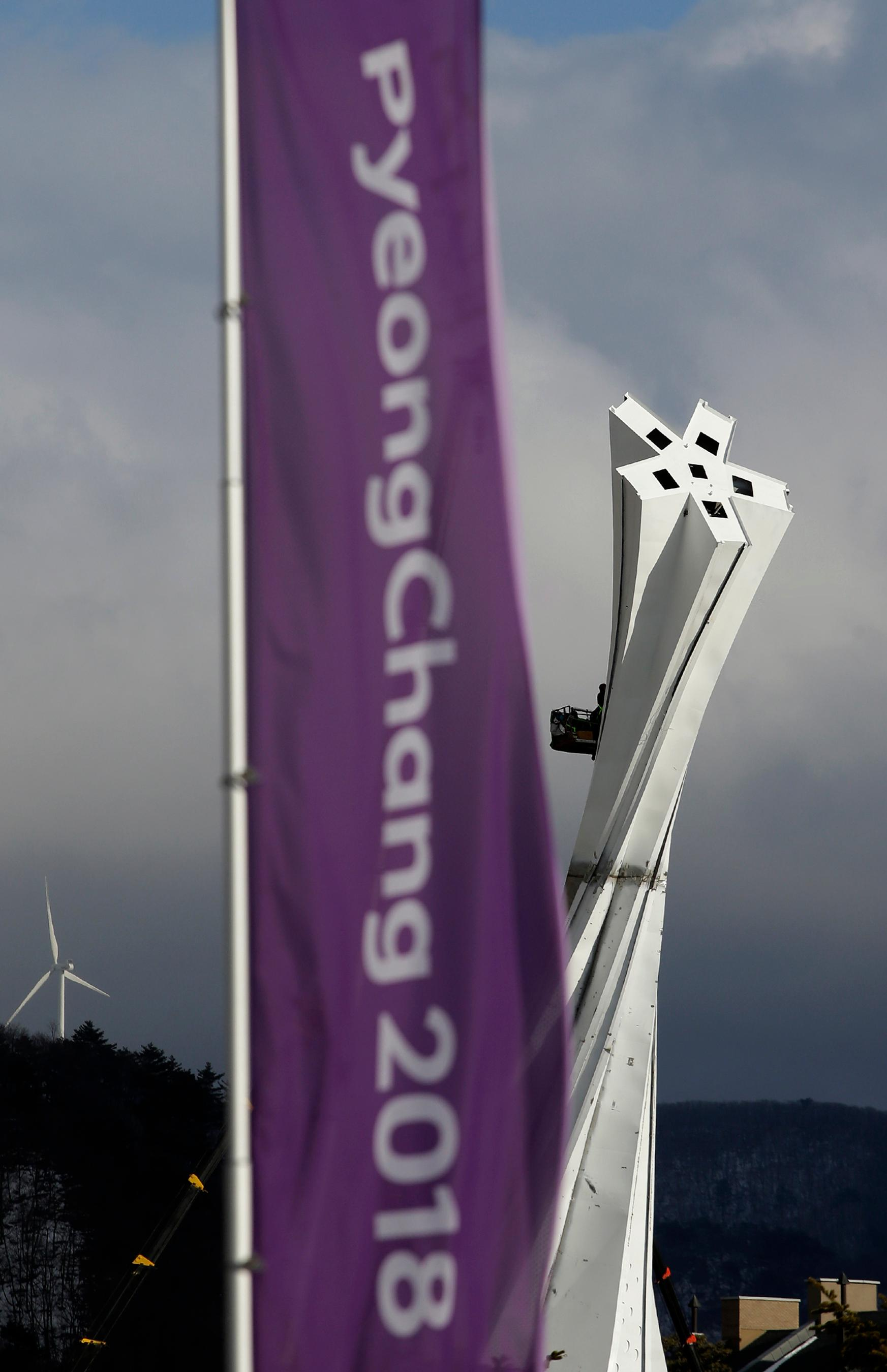 An Olympic Cauldron under construction rises beyond Olympic banners at the Alpensia resort at the 2018 Winter Olympics in Pyeongchang, South Korea, Friday, Feb. 2, 2018. (AP Photo/Charlie Riedel)