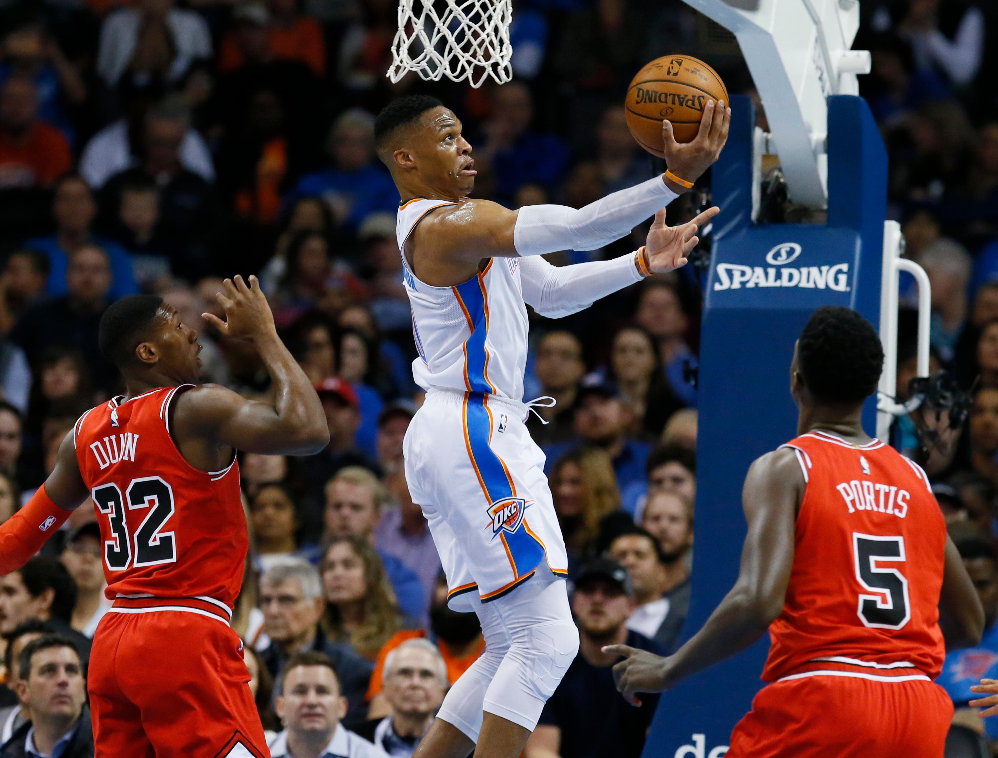 Oklahoma City Thunder guard Russell Westbrook, center, shoots between Chicago Bulls guard Kris Dunn (32) and forward Bobby Portis (5) in the first quarter of an NBA basketball game in Oklahoma City, Wednesday, Nov. 15, 2017. (AP Photo/Sue Ogrocki)