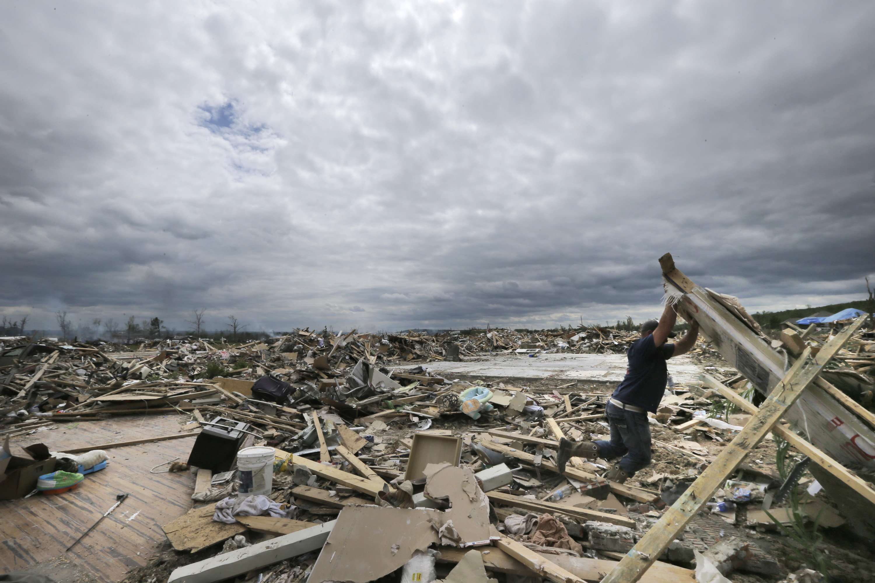 FILE - In this April 30, 2014, file photo, Dustin Shaw lifts debris as he searches through what is left of his sister's house at Parkwood Meadows neighborhood after a tornado in Vilonia, Ark. A new study finds that tornado activity is generally shifting eastward to areas just east of the Mississippi River that are more vulnerable such as Mississippi, Arkansas and Tennessee. And it's going down in Oklahoma, Kansas and Texas. (AP Photo/Danny Johnston, File)