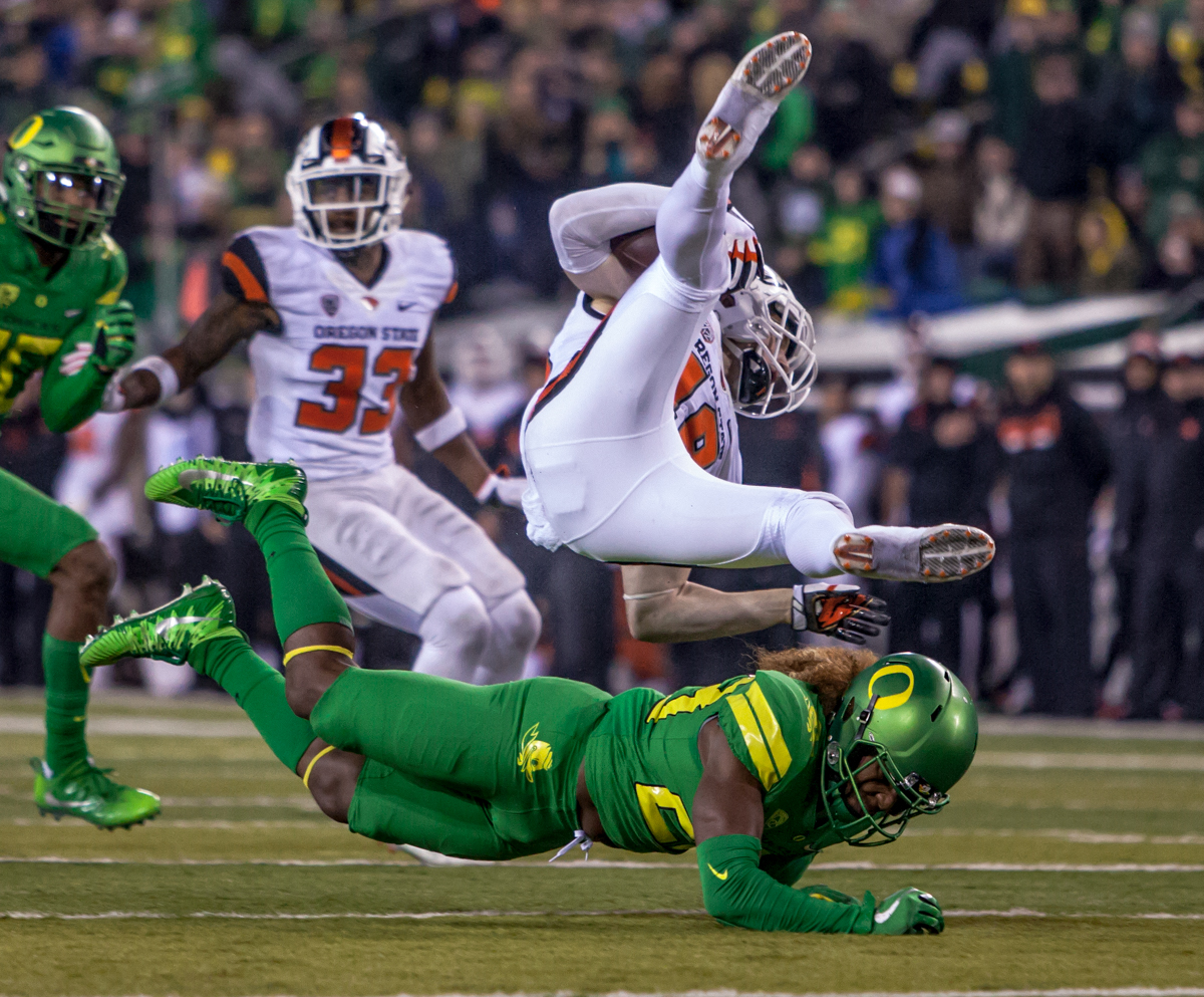 Oregon state wide receiver Timmy Hernandez (#18) falls over Oregon defensive player Mike Lovett (#23). The Oregon Ducks defeated the Oregon State Beavers 69 to 10 in the 121st Civil War game at Autzen Stadium in Eugene, Ore. on Saturday November 25, 2017. Photo by Ben Lonergan, Oregon News Lab
