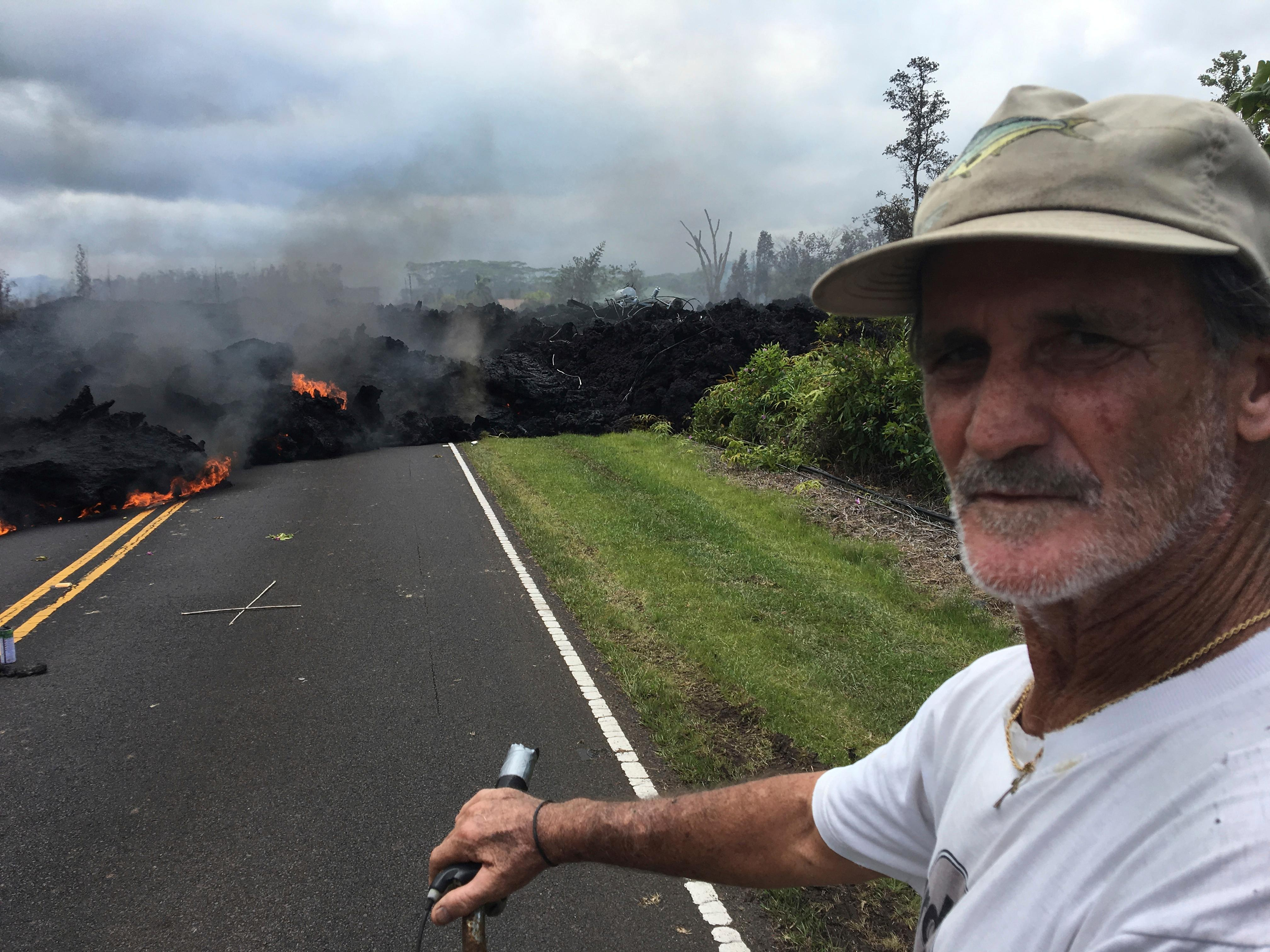 Resident Sam Knox, 65, rides his bicycle to the edge of the road as lava burns across the road in the Leilani Estates in Pahoa, Hawaii, Saturday, May 5, 2018. Hundreds of anxious residents on the Big Island of Hawaii hunkered down Saturday for what could be weeks or months of upheaval as the dangers from an erupting Kilauea volcano continued to grow. Lava spurted from volcanic vents, toxic gas filled the air and strong earthquakes, including a magnitude 6.9 temblor on Friday, rocked an already jittery population. (AP Photo/Marco Garcia)