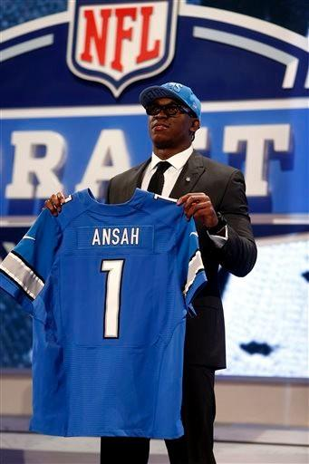 Ezekiel Ansah, from Brigham Young, holds up a team jersey after being selected fifth overall by the Detroit Lions in the first round of the NFL football draft, Thursday night.