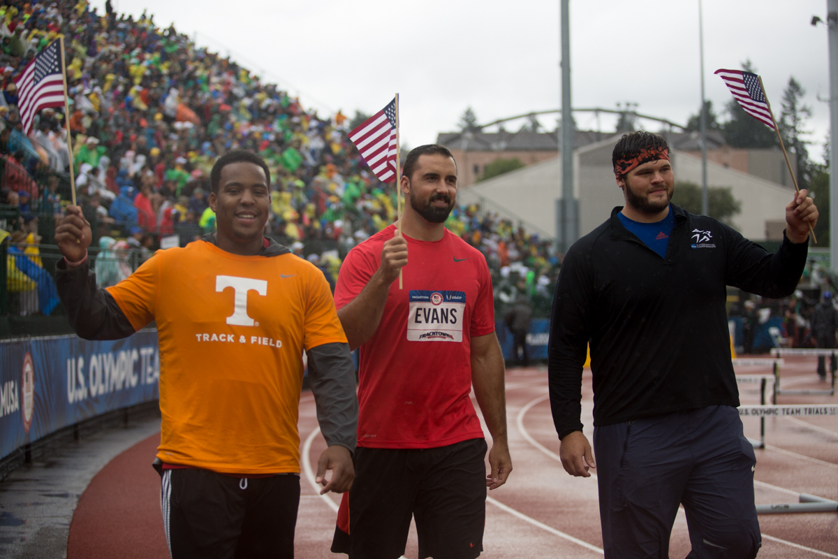 The top three finishers in the men�s discus throw take their victory lap in the rain. Photo by Dillon Vibes