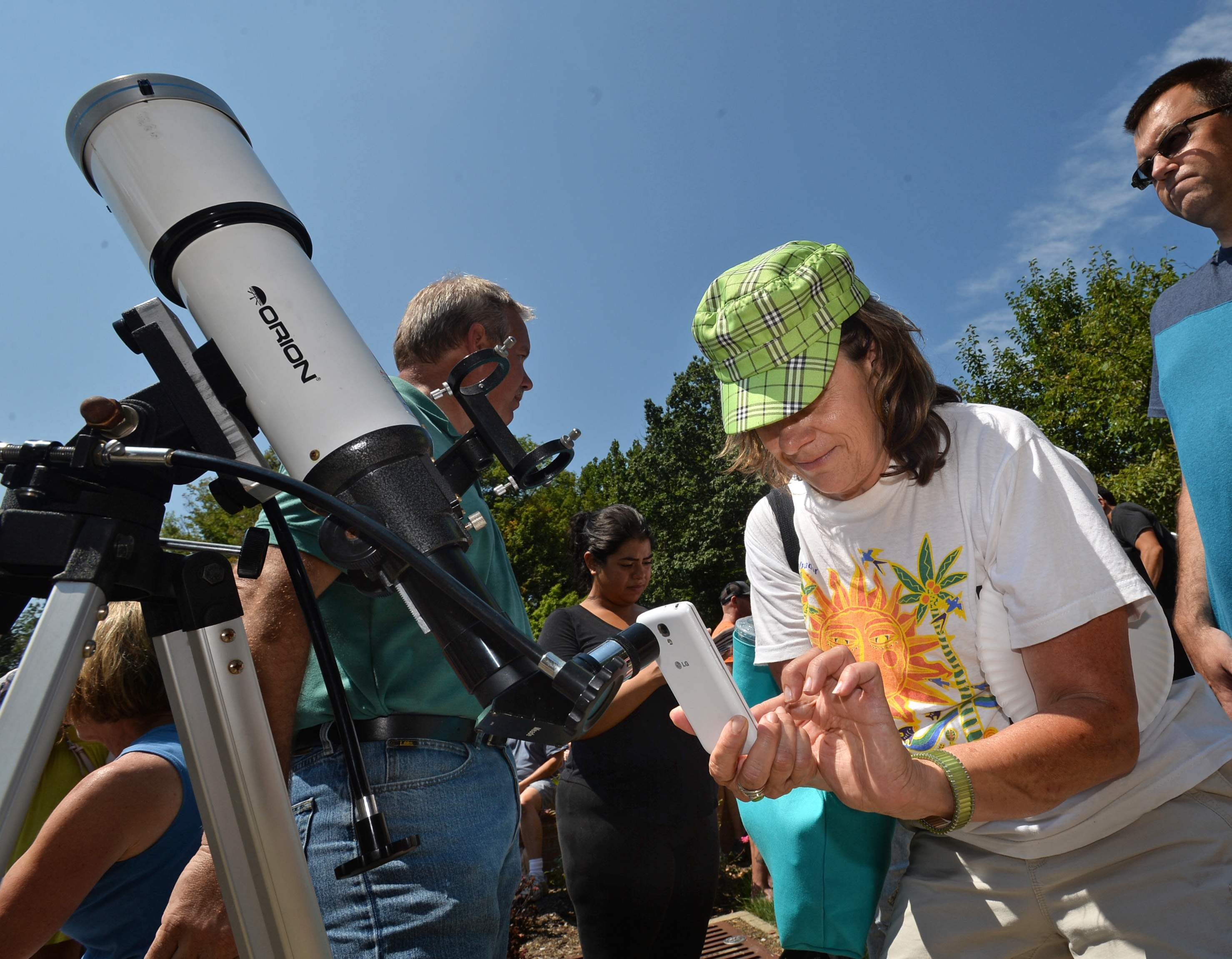 Lydia Chimenti of Erie photographs the eclipse with her smart phone Aug. 21 at an eclipse-viewing party held at Penn State Behrend in Harborcreek Township. Hundreds turned out for the event, which featured telescopes fitted with solar filters available for viewing the partial eclipse. [CHRISTOPHER MILLETTE/ERIE TIMES-NEWS]