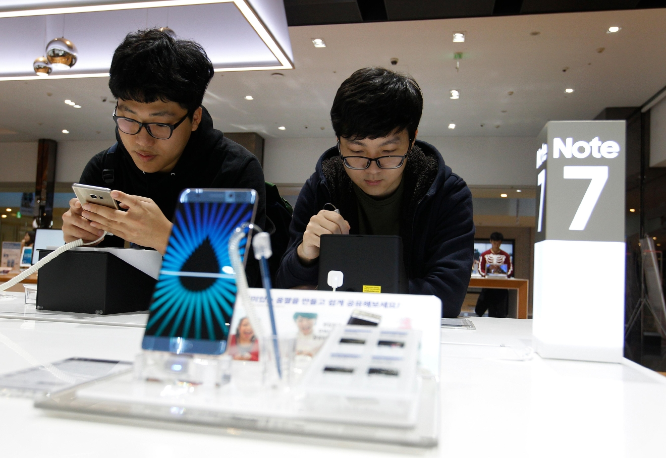 South Korean high school students try out Samsung Electronics Galaxy Note 7 smartphones at the company's shop in Seoul in Seoul, South Korea, Monday, Oct. 10, 2016. Samsung Electronics has temporarily halted production of its Galaxy Note 7 smartphones, South Korea's Yonhap news agency reported Monday, following reports that replacements for the fire-prone phones were also overheating. (AP Photo/Ahn Young-joon)