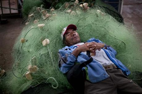 A small scale fisherman naps on a jumble of fishing nets in Lima, Peru, Wednesday, April 2, 2014.