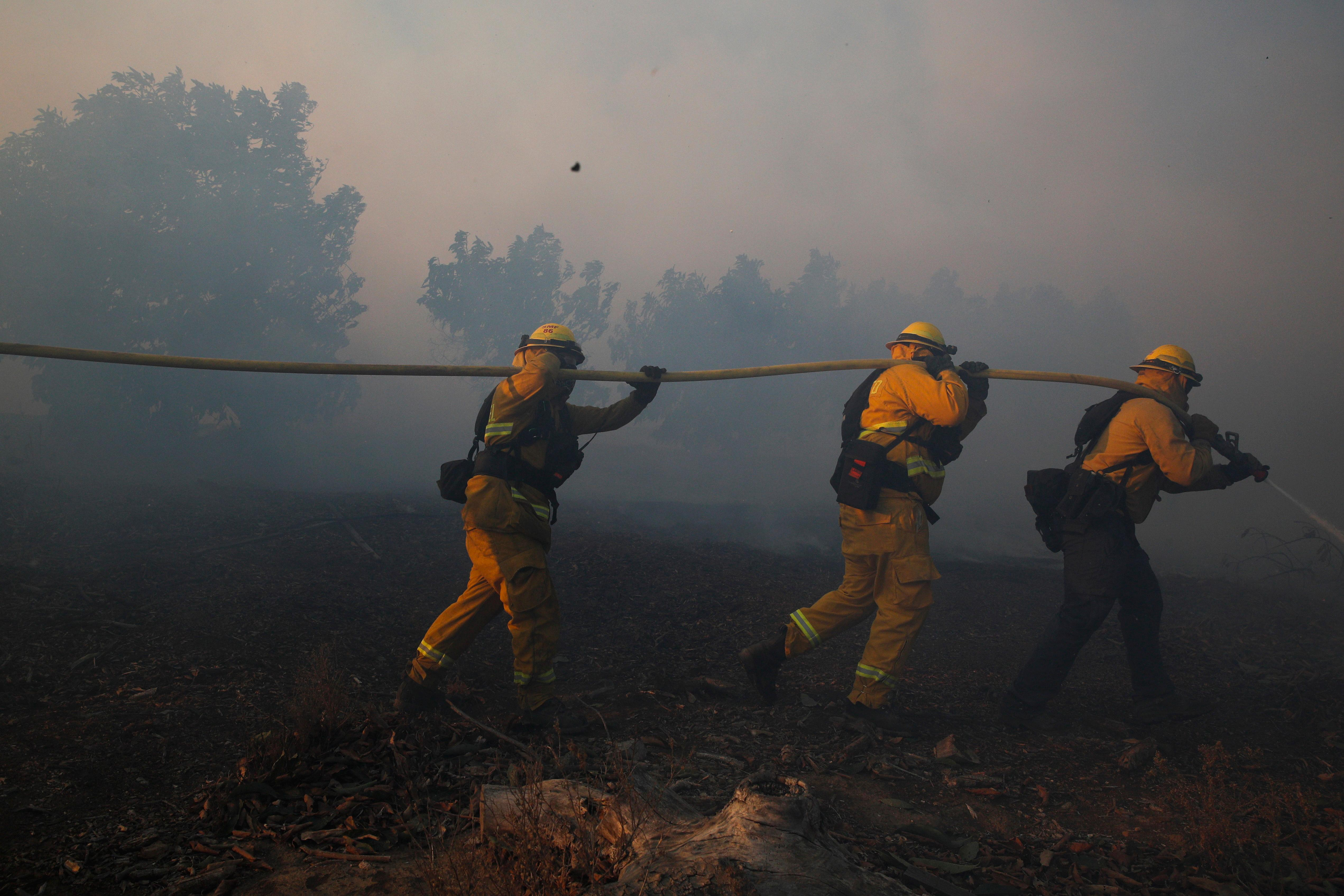 Firefighters put out a wildfire burning in an orchard Tuesday, Dec. 5, 2017, in Santa Paula, Calif. Raked by ferocious Santa Ana winds, explosive wildfires northwest of Los Angeles and in the city's foothills burned a psychiatric hospital and scores of homes and other structures Tuesday and forced the evacuation of tens of thousands of people. (AP Photo/Jae C. Hong)